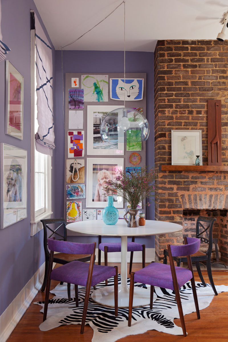 Works by the kids are displayed in the dining nook alongside framed photographs and a minimalist light fixture.