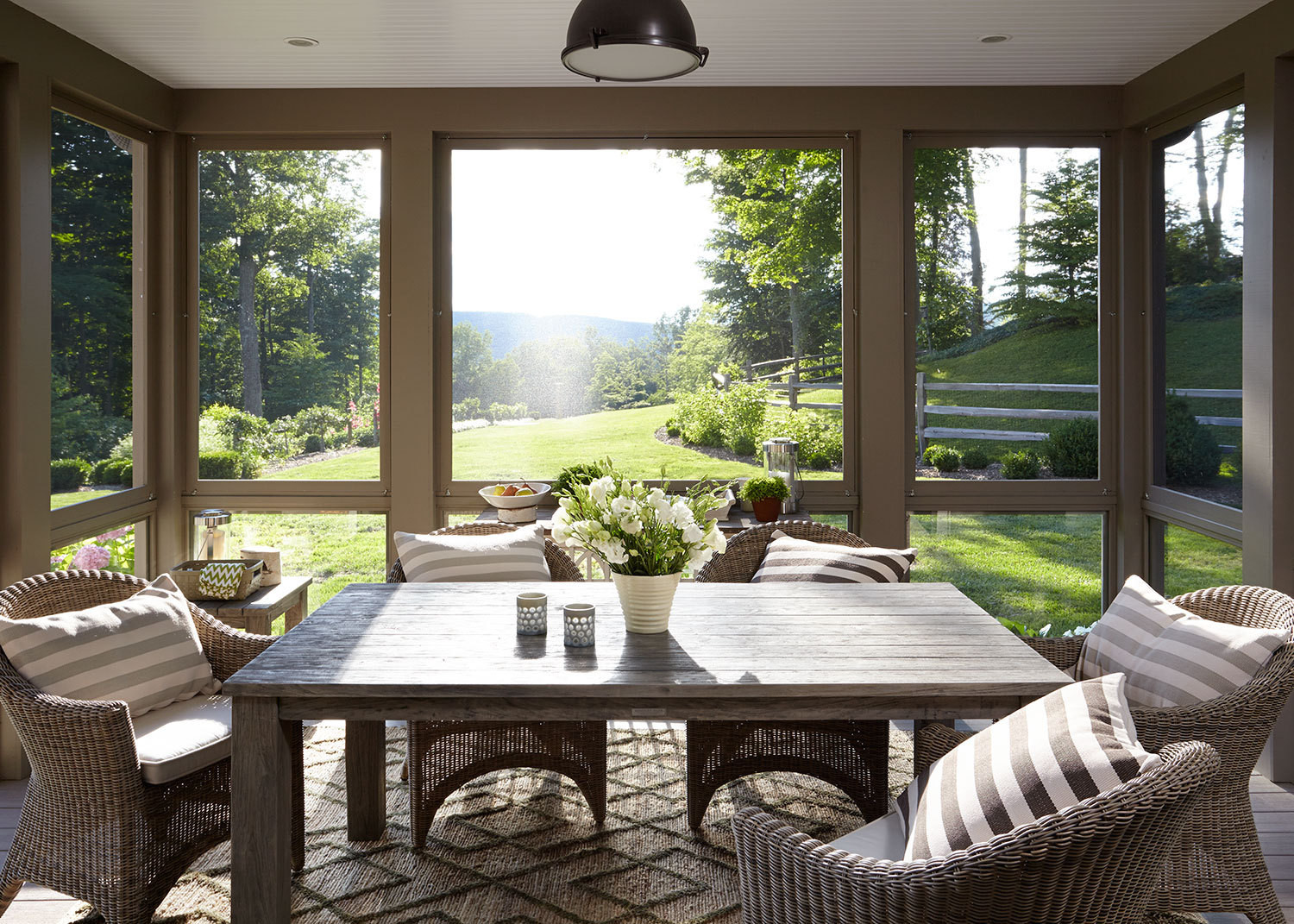 The renovation places an emphasis on indoor-outdoor living: this screened porch, furnished with a table and chairs from Kingsley Bate, is used in three seasons.