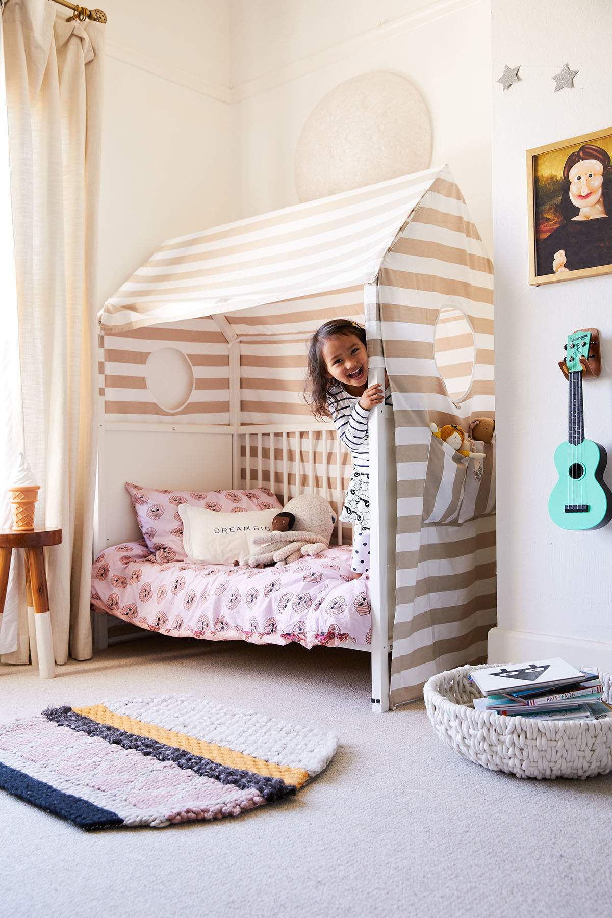 Tallie's playful bedroom is a dreamy, neutral retreat. Serena & Lily Stool | Barn & Willow Custom Drapes | Stokke Bed | Hugo Loves Tiki x Kip & Co Bedding | HillHouse Home Pillow | Justina Blakeney x Pottery Barn Kids Collection Moon | Larry Moss Art.