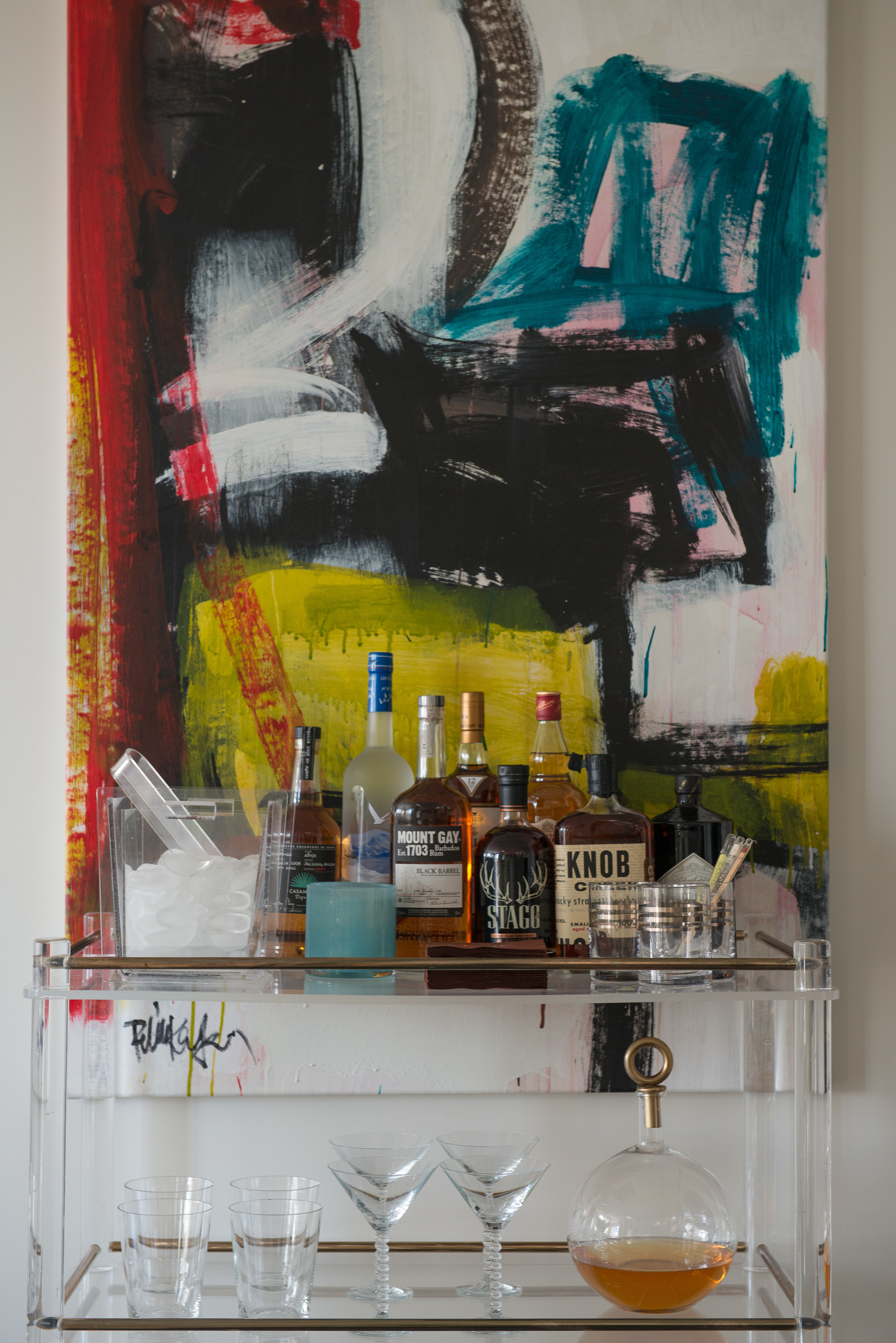 "Stearns keeps her midcentury French bar cart stocked with barware and bottles. A large painting by Robbie Kemper hangs behind it. ""I just love the color and freeness of the brush strokes,"" the designer says of the contemporary piece."