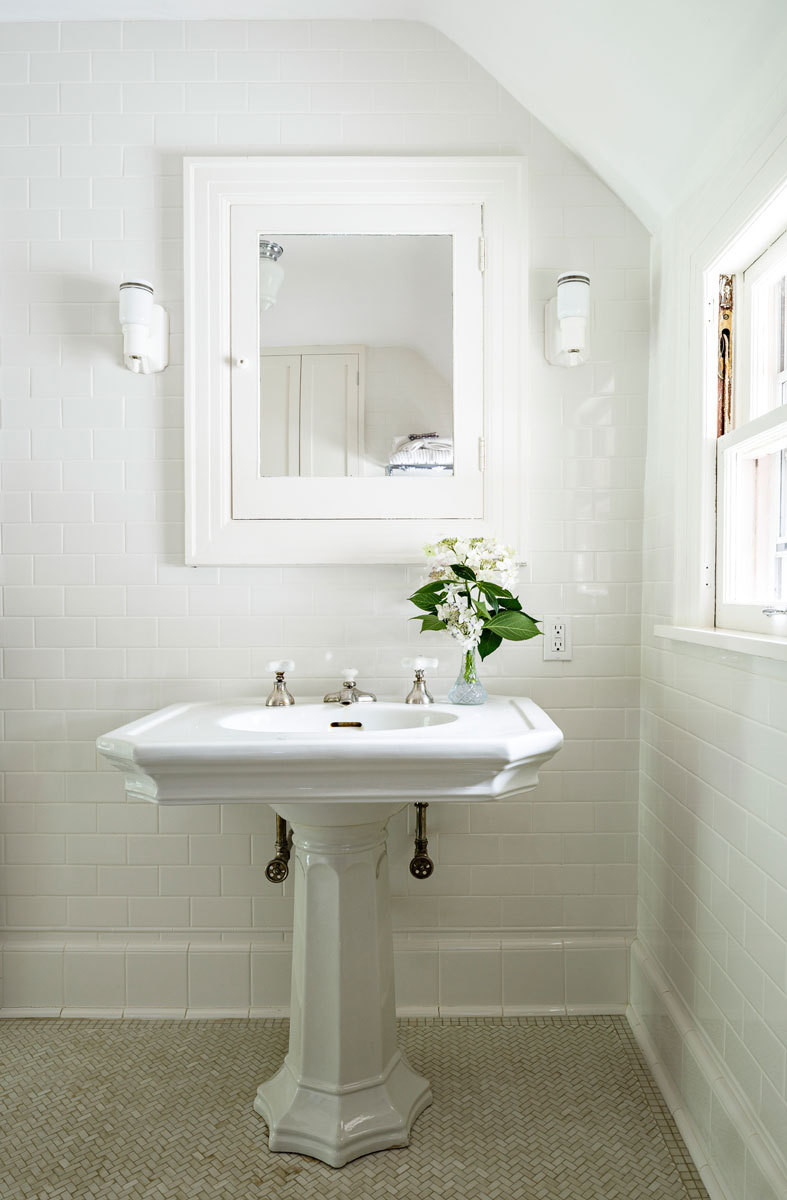 Classic tile, sconces, and a pedestal sink reinforce the home's early-20th-century qualities.