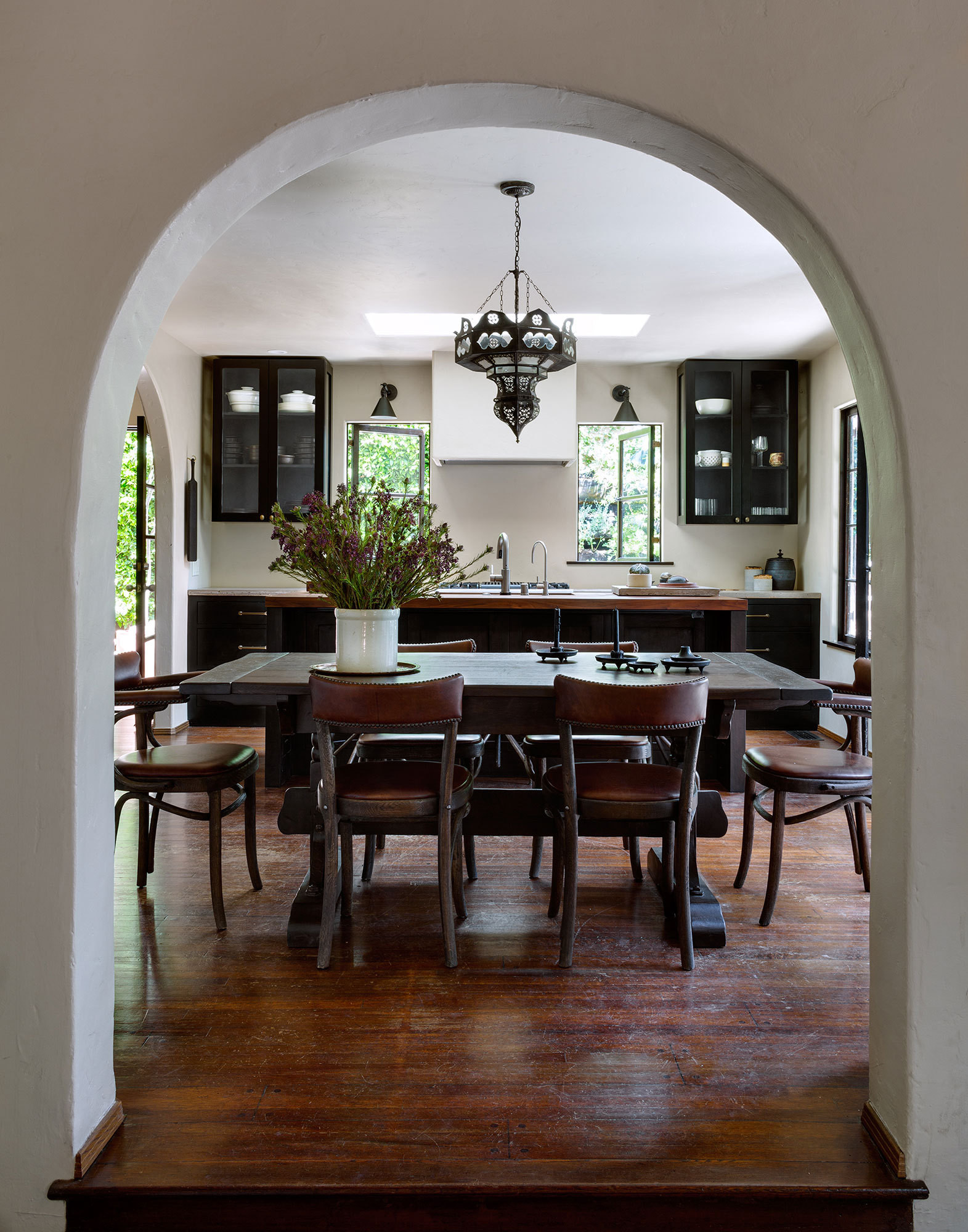 A traditional arched doorway leads to the dining area and kitchen.