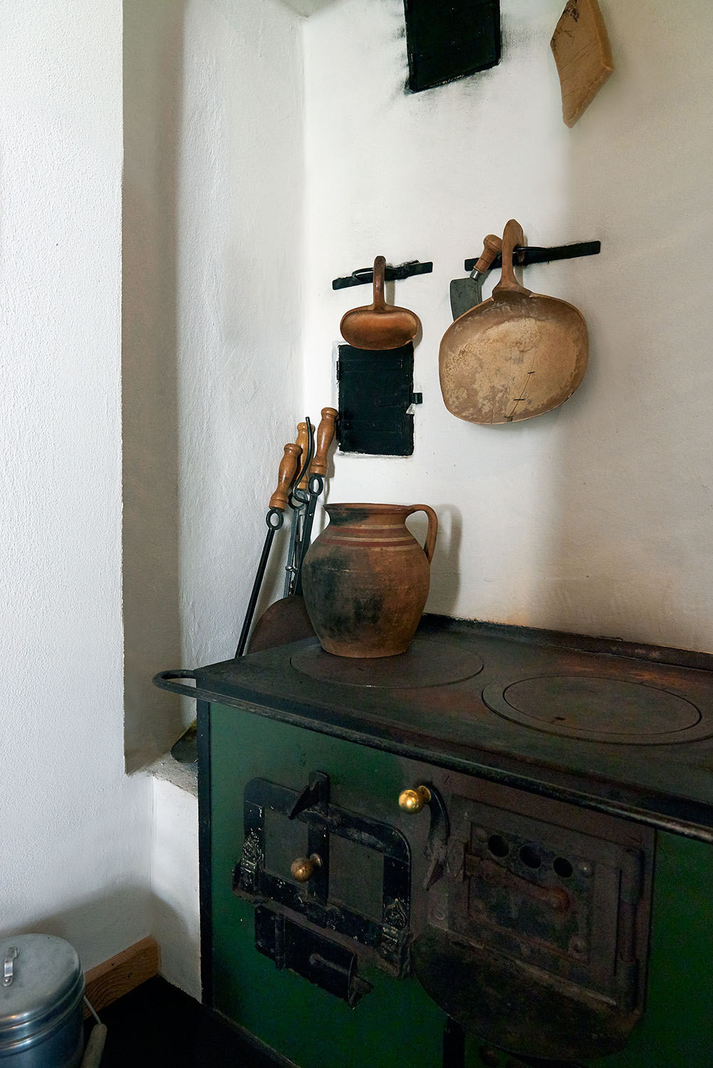 Antique utensils and ceramics top the circa-1850 wood-burning stove, a stately presence in the entryway.