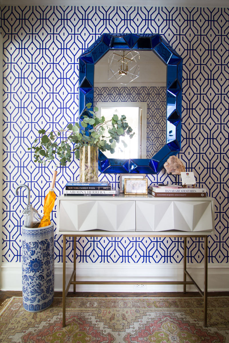 A graphic Anna Spiro wallpaper and jewel-like mirror from Bungalow 5 combine to dazzling effect in the entryway.