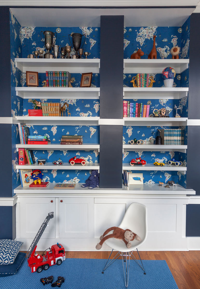 Map wallpaper is mounted behind the playroom's built-in shelves.