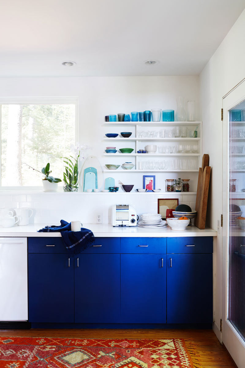 A strong color for the kitchen cabinetry helps ground the white-walled space.