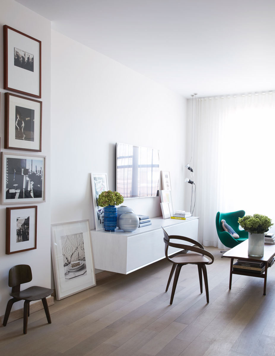 Hung vertically, black-and-white photos create an impactful display, in the living room.