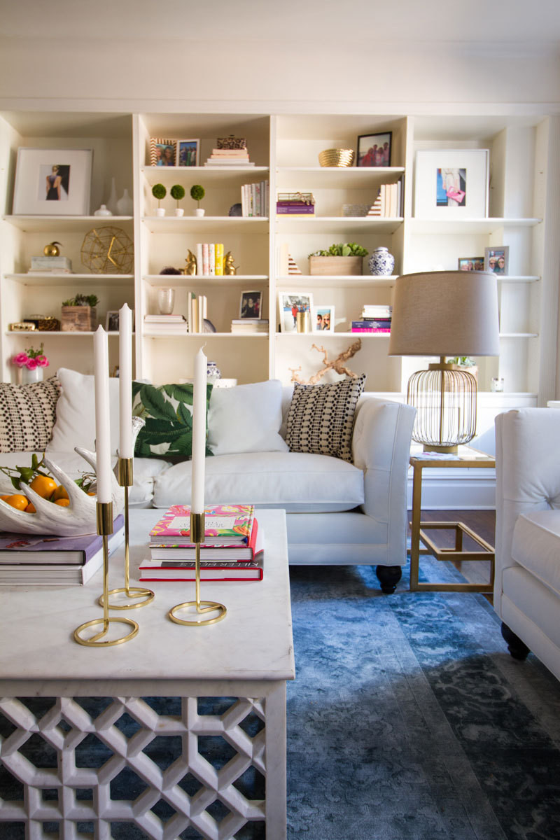 In the living room, a trellis-inspired coffee table and curvaceous brass candlesticks marry preppy and modern styles.