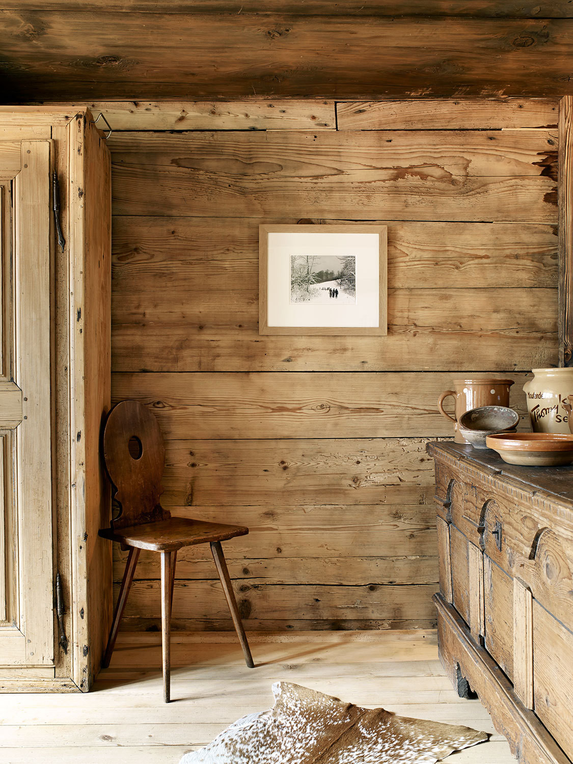Another hutch, left in the house by the previous owners, anchors one corner of the dining area near an antique farmer's chair, a series of Swiss and Austrian ceramics, and a photograph by Hans Baumgartner.