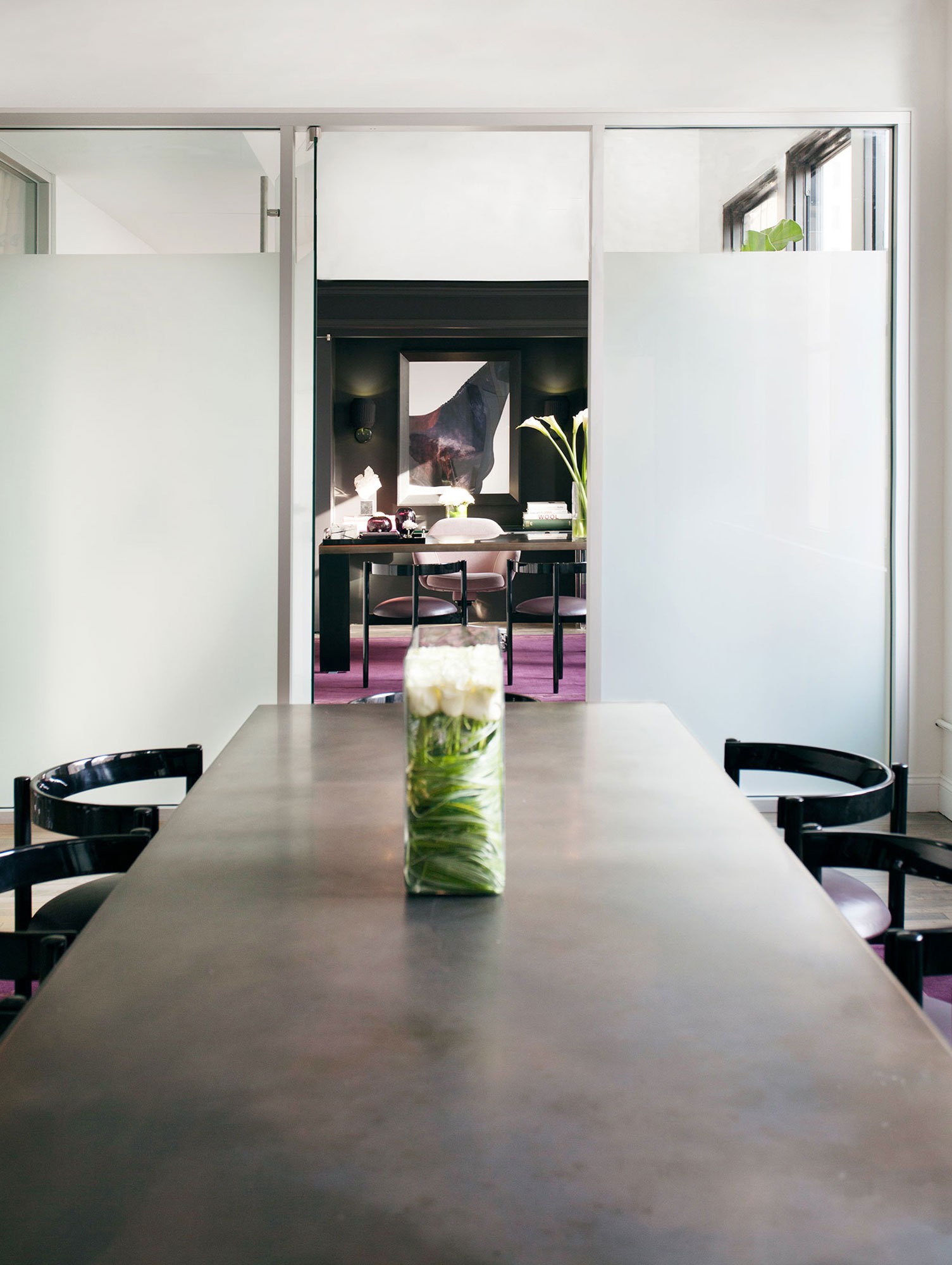 Black chairs surround a sleek conference table near the office's reception area.