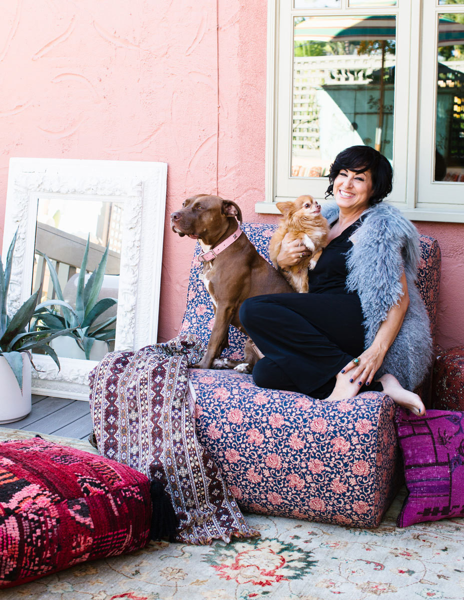 The designer relaxes in her outdoor living room, with the family's red-nosed pitbull, Mocha, and Foxy, a long-haired Chihuahua.