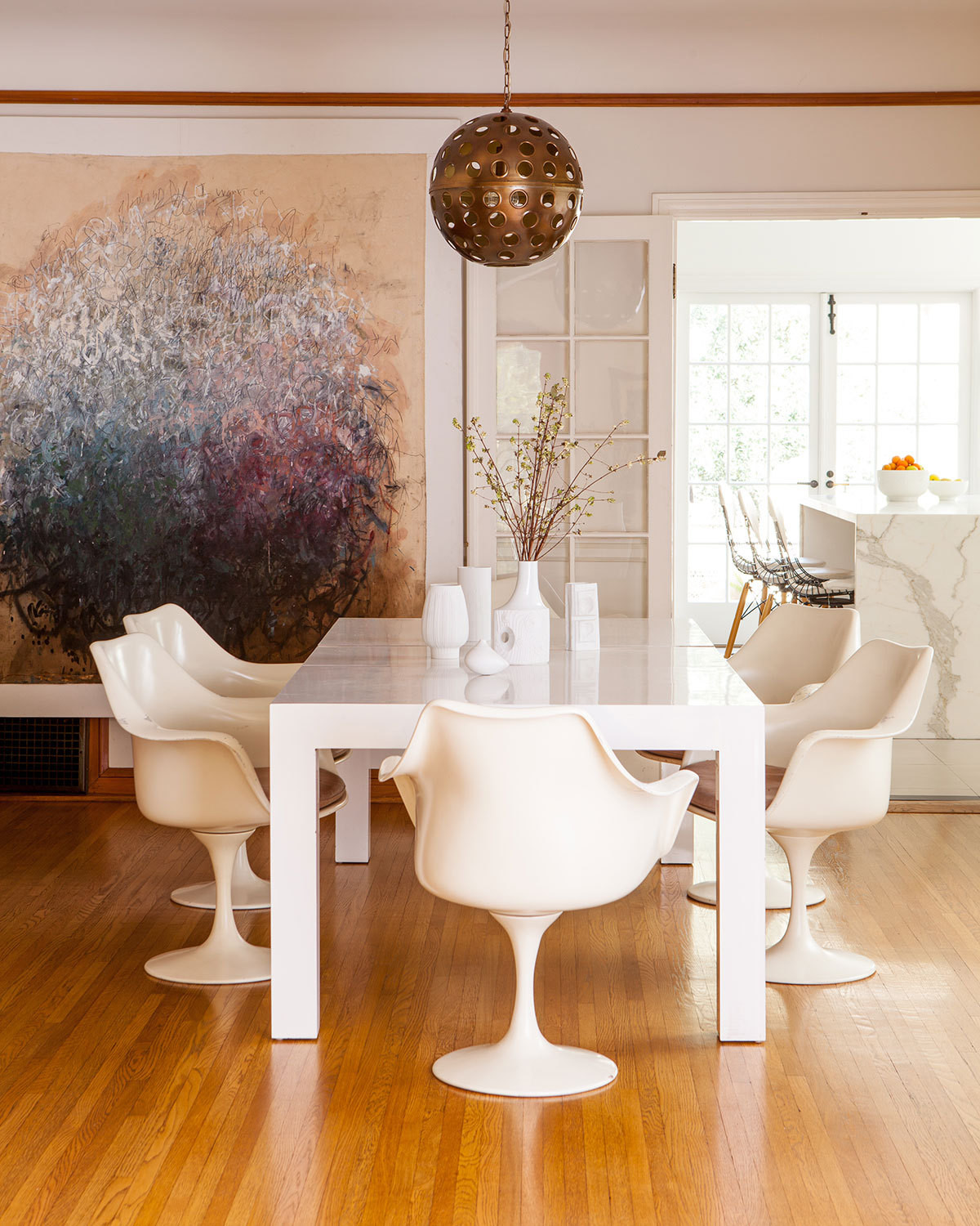 The white dining table is a midcentury Milo Baughman purchased on Craigslist. The Tulip chairs are by Eero Saarinen.