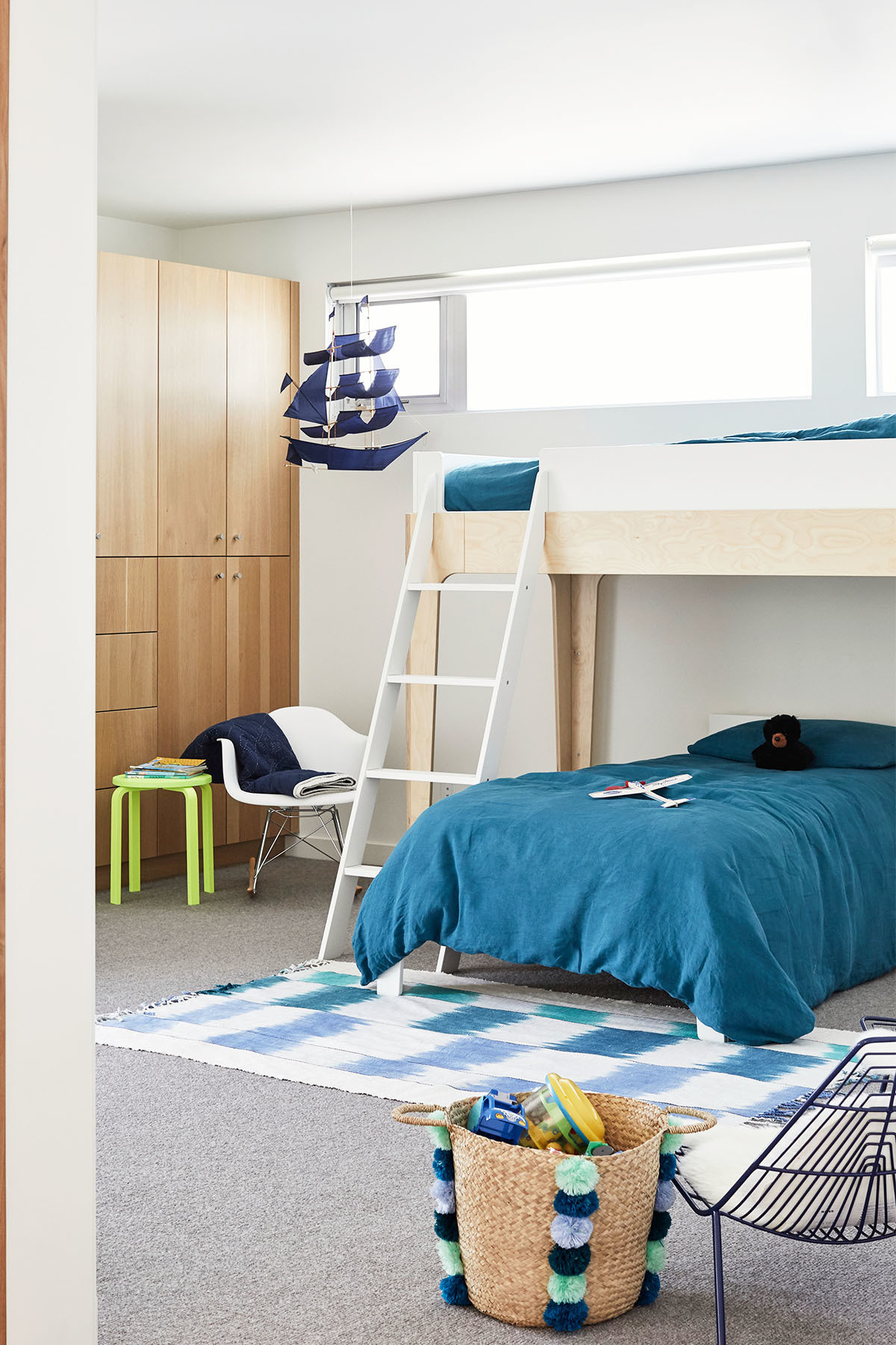 The casual kids room adds a pop of color to the Merrill family beach house. Oeuf Bunk Beds | Caroline Z Hurley Rug | Crate and Barrel Baskets | DWR Chair | Marshall Laplante Art | Oeuf Ladder | LinenMe Bedding | IKEA Bedside Table | Crate and Barrel Chair.
