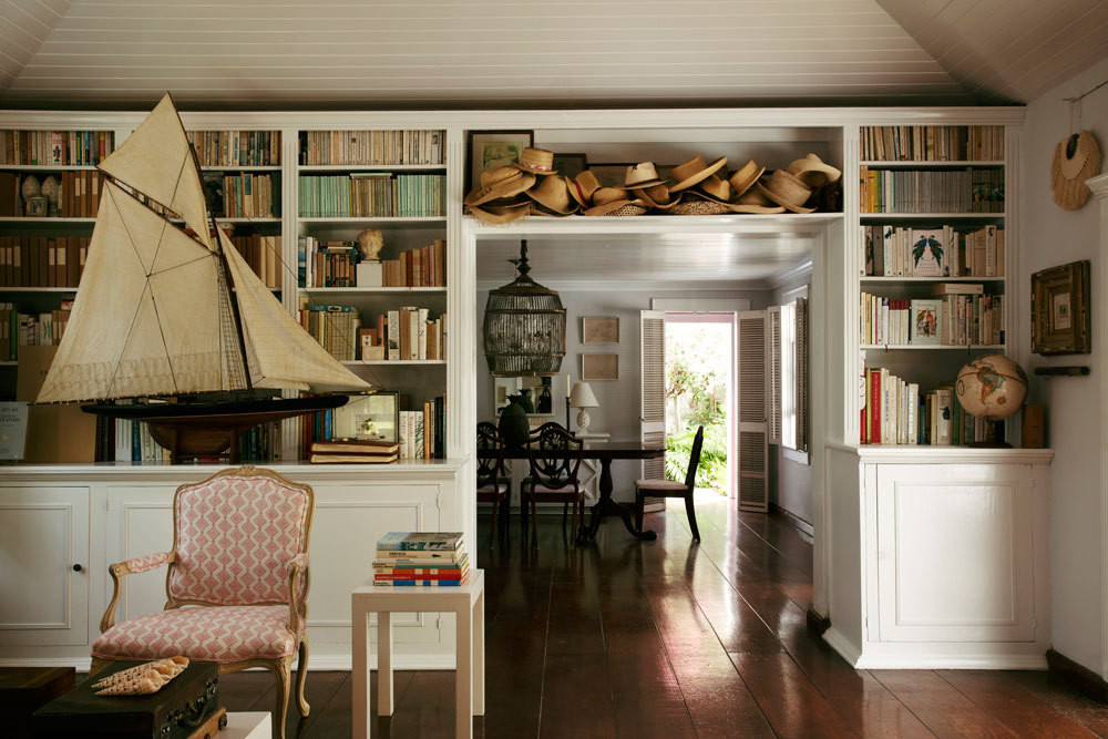 Shelves of books and a lending library of straw hats line the walls of Hibiscus Hill's sitting room. All images courtesy of Rizzoli International Publications, Inc.