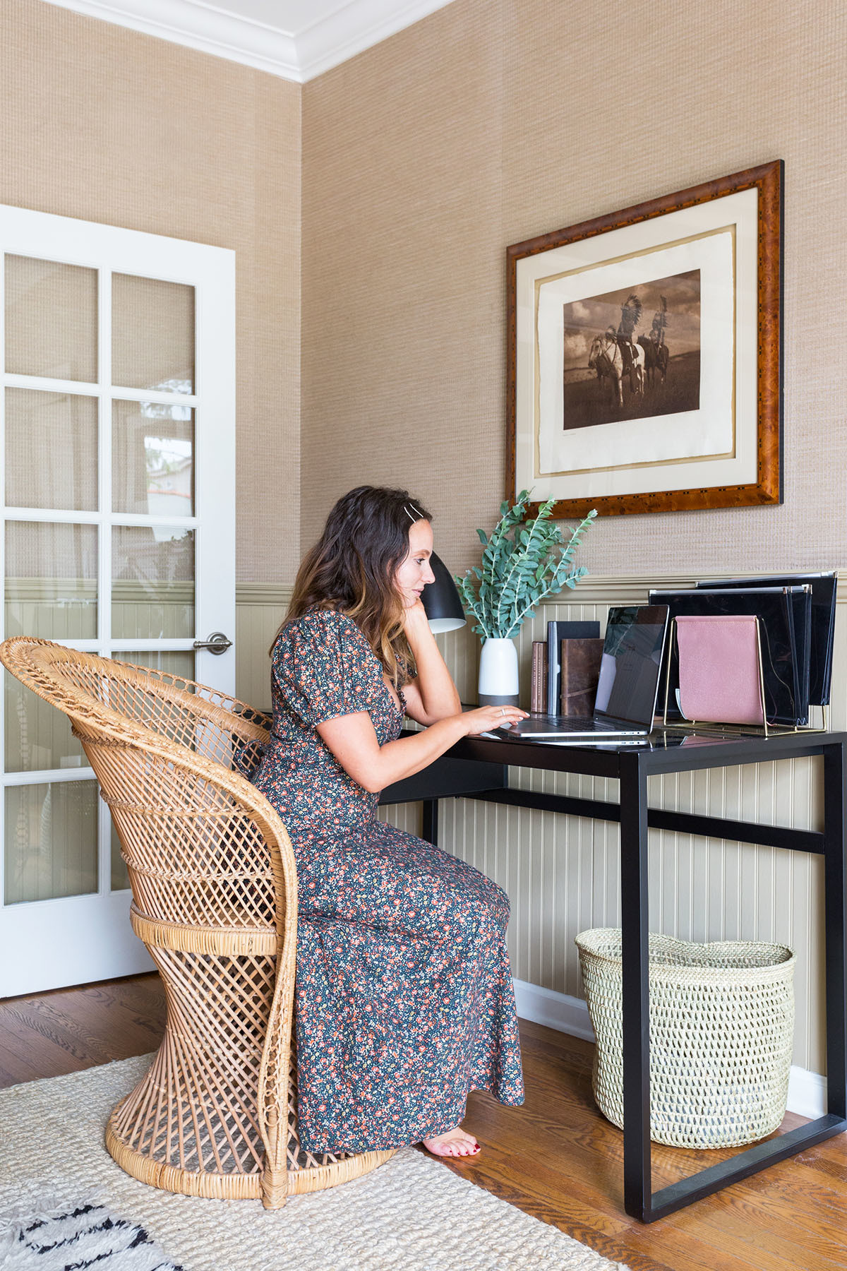 The designer created a study nook to ensure she could comfortably work from home, using an Urban Outfitters rattan chair and a minimal desk by AllModern. Anthropologie File Holder.