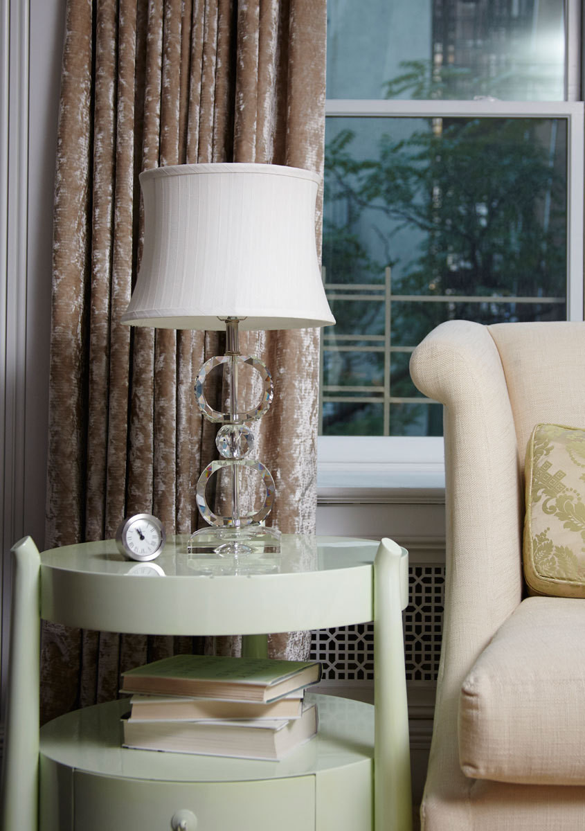 Opposite the bed, a mint-green vintage side table is topped with a Lucite table lamp.