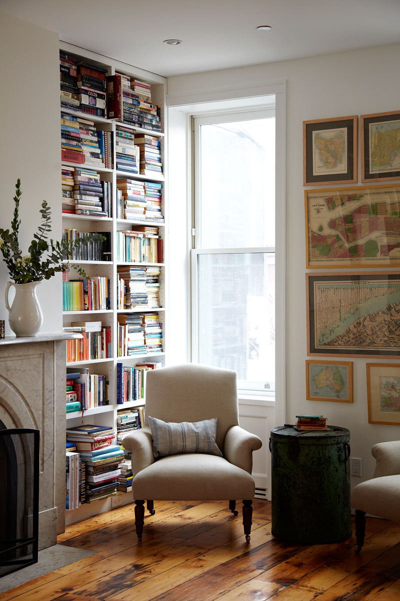 Custom bookshelves and a wall of framed maps create a cozy reading nook.