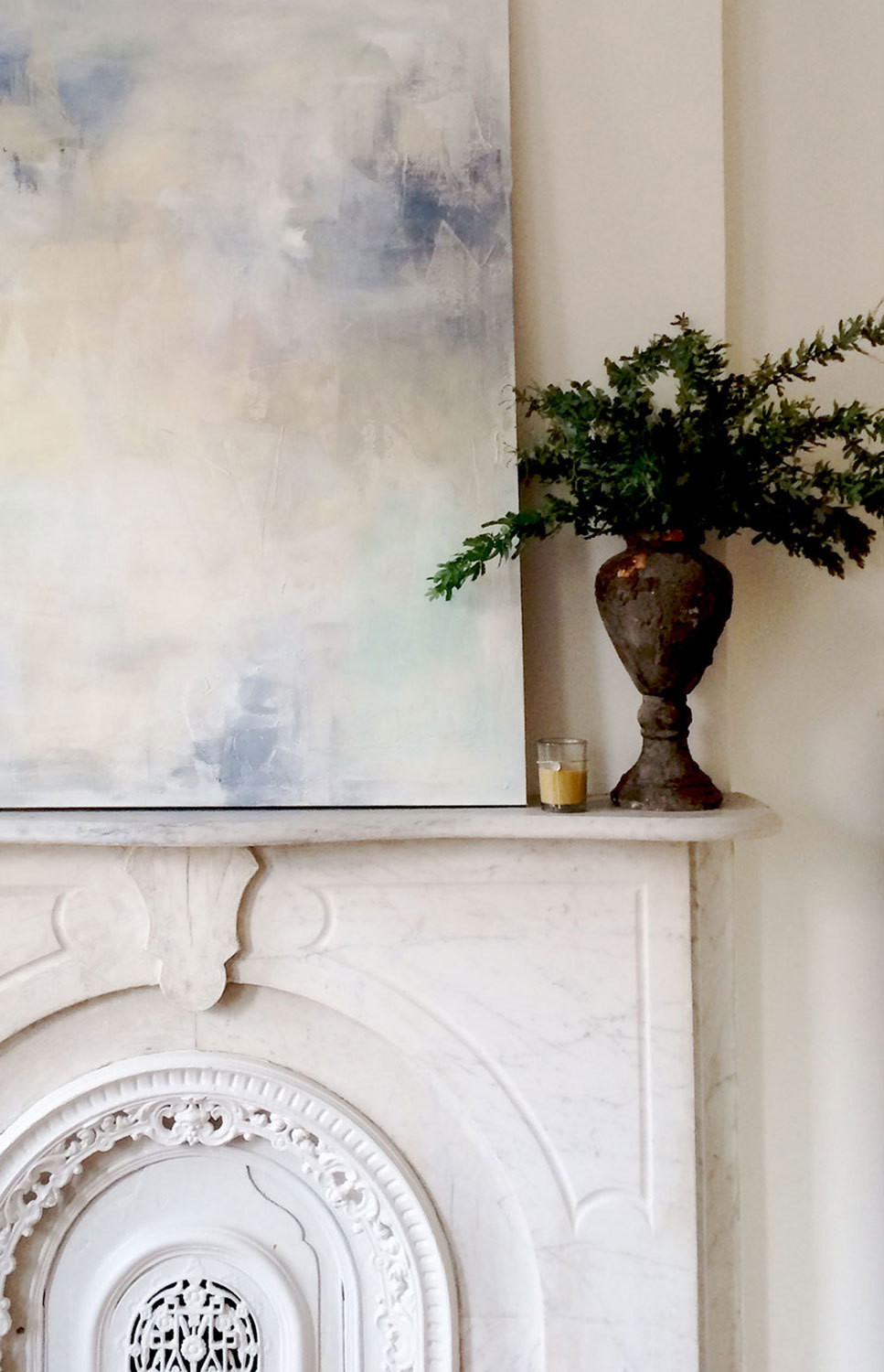 A painting by artist Julia Contacessi sits on the ornate mantel.