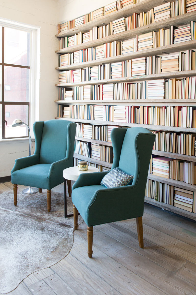 A wall of floor-to-ceiling bookshelves provide a three-dimensional backdrop to two emerald-covered armchairs.