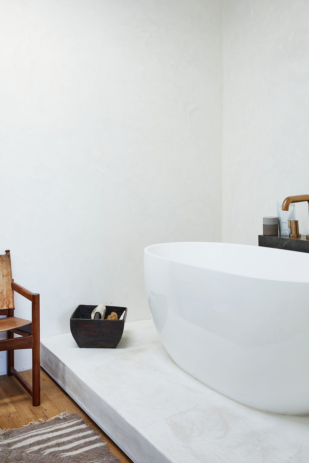 """I love the open floor plan of my bathroom,"" Pelayo explains. ""I also really love taking a baths — shocking, I know, since our business grew out of the ritual of bathing. To me though, this space is my sanctuary, a place to reset both body and mind."" 1stdibs Vintage Armchair 