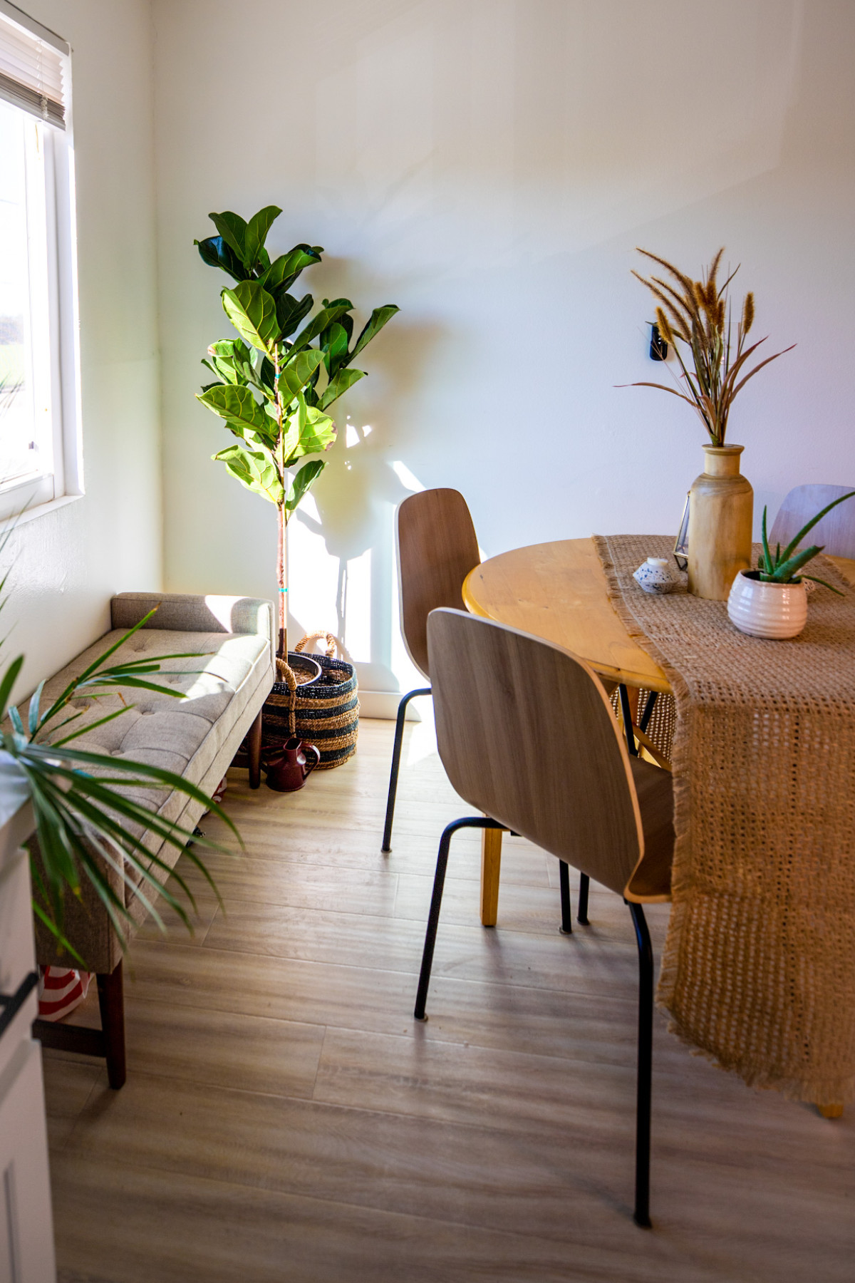 A neutral paletteis balanced out by lively houseplants inthe dining room.Facebook MarketplaceTable|TargetChairs|TargetBasket |Target Runner |World Market Vases |Goodwill Bench. Photographed by Cher Martinez for Lonny.