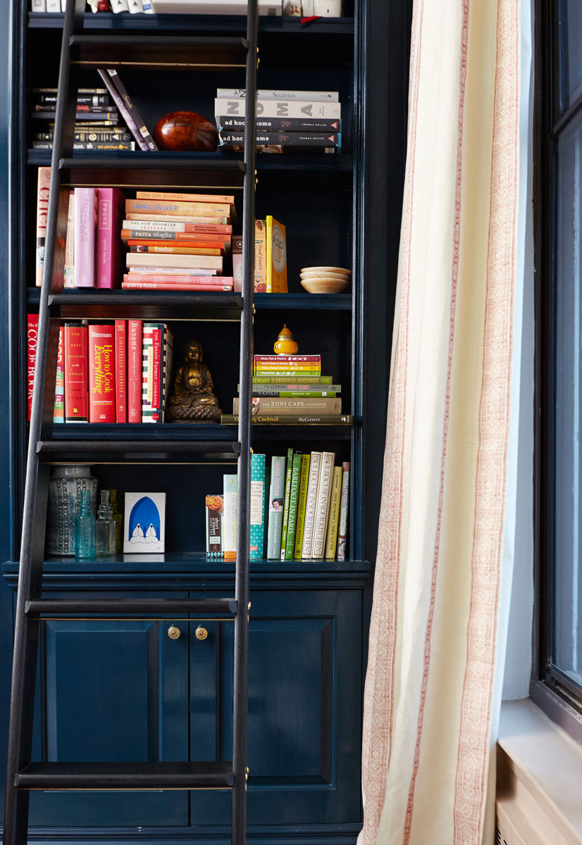 A rolling ladder allows for easy access to the built-in cabinetry's higher shelving in the living room.