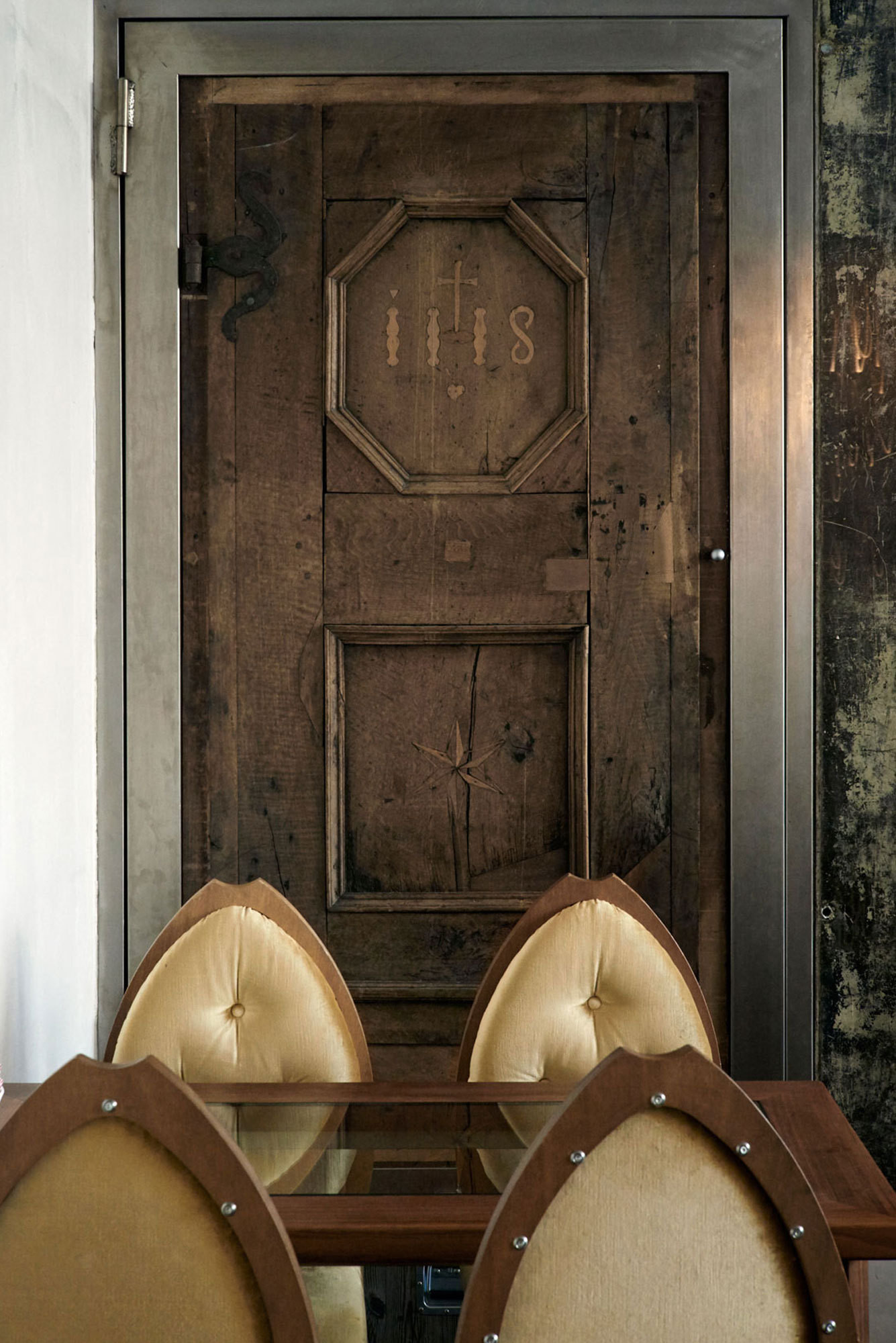 Rococo walnut chairs in the hotel restaurant offset a rustic door salvaged from a centuries-old chalet.