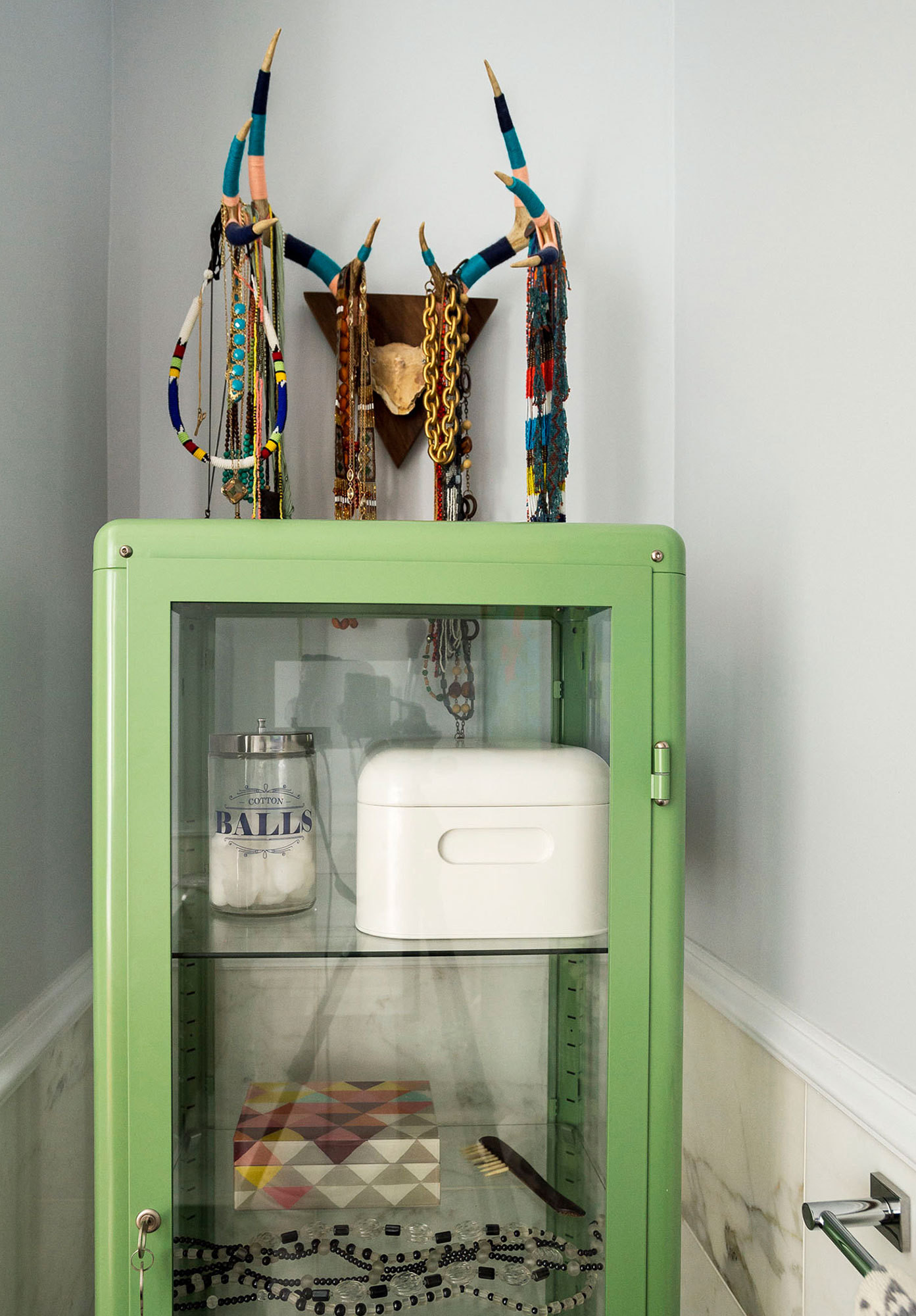 A colorful jewelry display enlivens a quiet corner in a shared gray-hued bathroom.