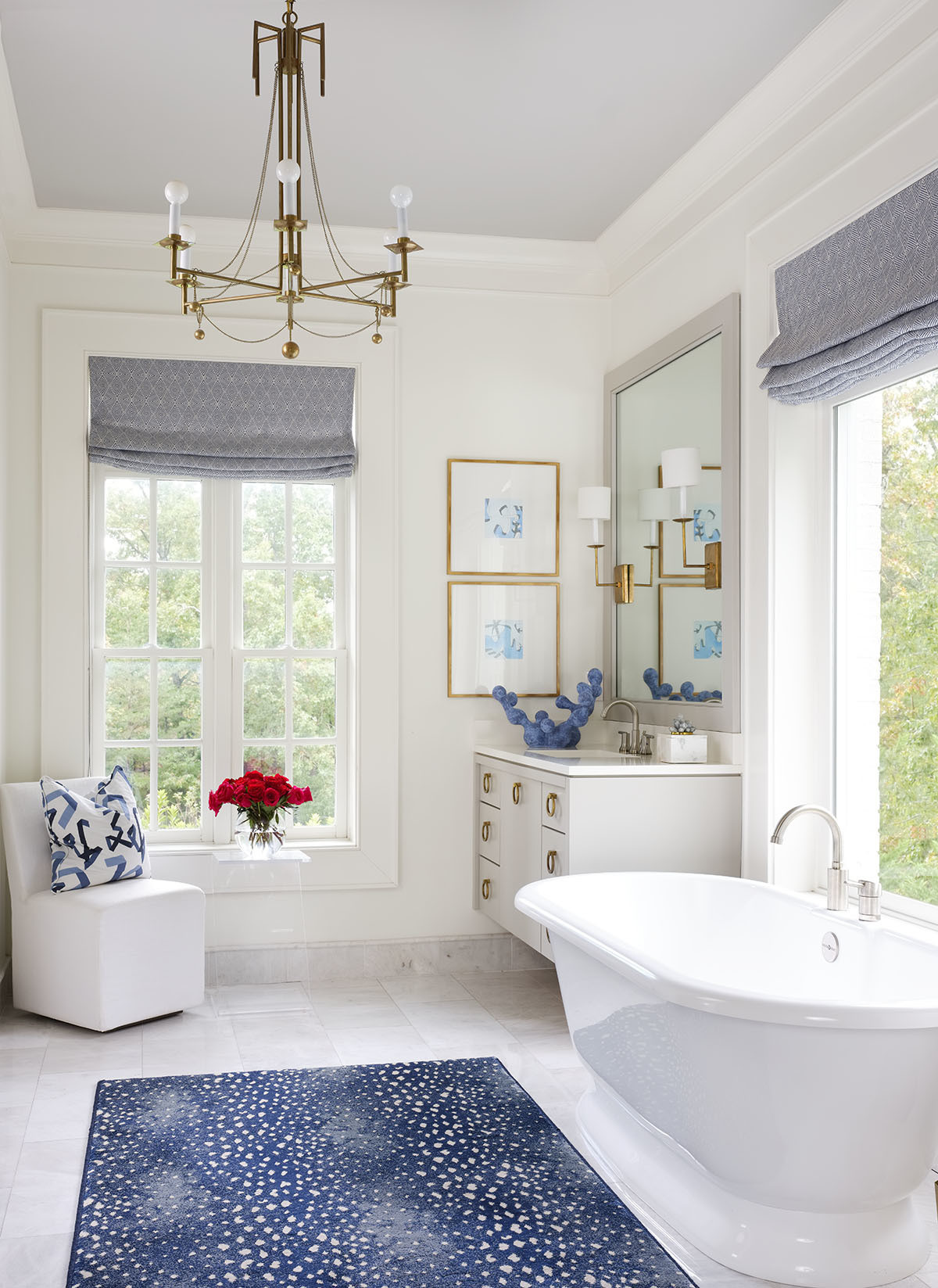 Simplicity is key in the serene bathroom with muted hues of blue and metallic accents. Victoria & Albert Bathtub | Custom Shades |Stark Studio Runner | Custom Cabinetry | Custom Mirror |Circa Lighting Pendant and Sconce Lights |Restoration Hardware Side Chair |