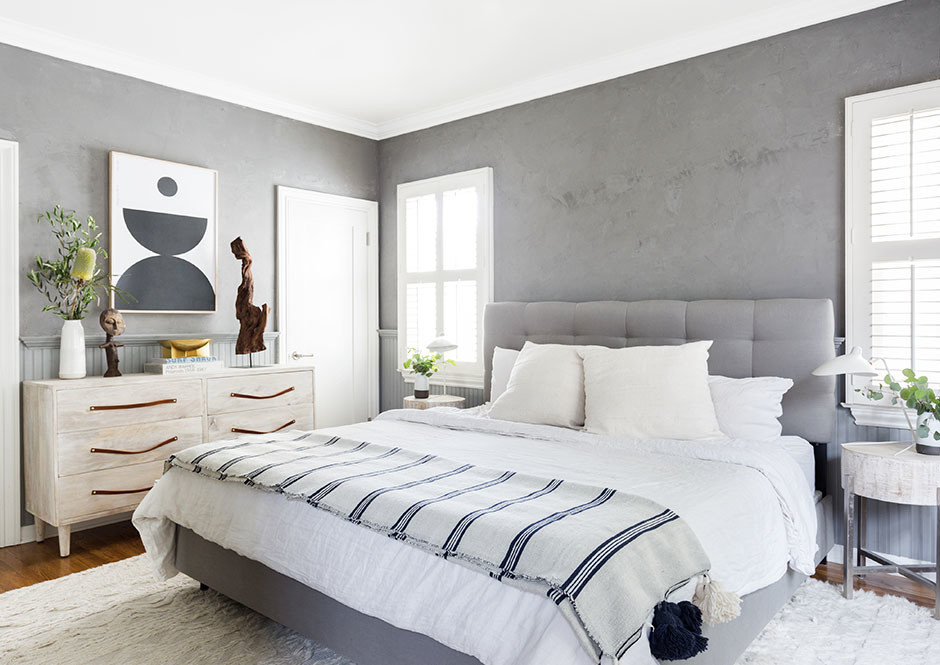 Margolis gave the master bedroom a dramatic upgrade, by swapping out her bed and painting the walls a stoney shade of slate gray. Vintage Rug | Urban Outfitters Dresser | Parachute Home Bedding | Portola Paints & Glazes Paint.