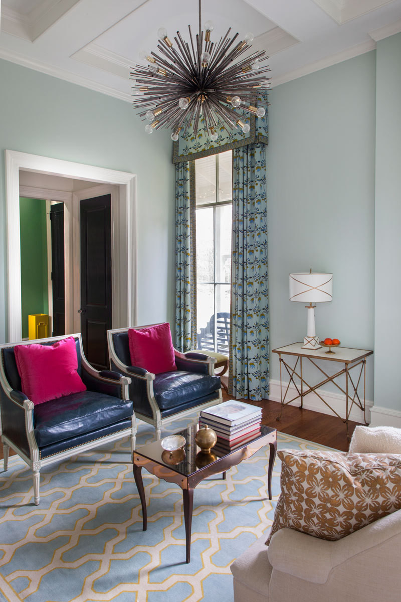 The intimately sized living room is home to a pair of French bergère chairs reupholstered in mottled navy leather.