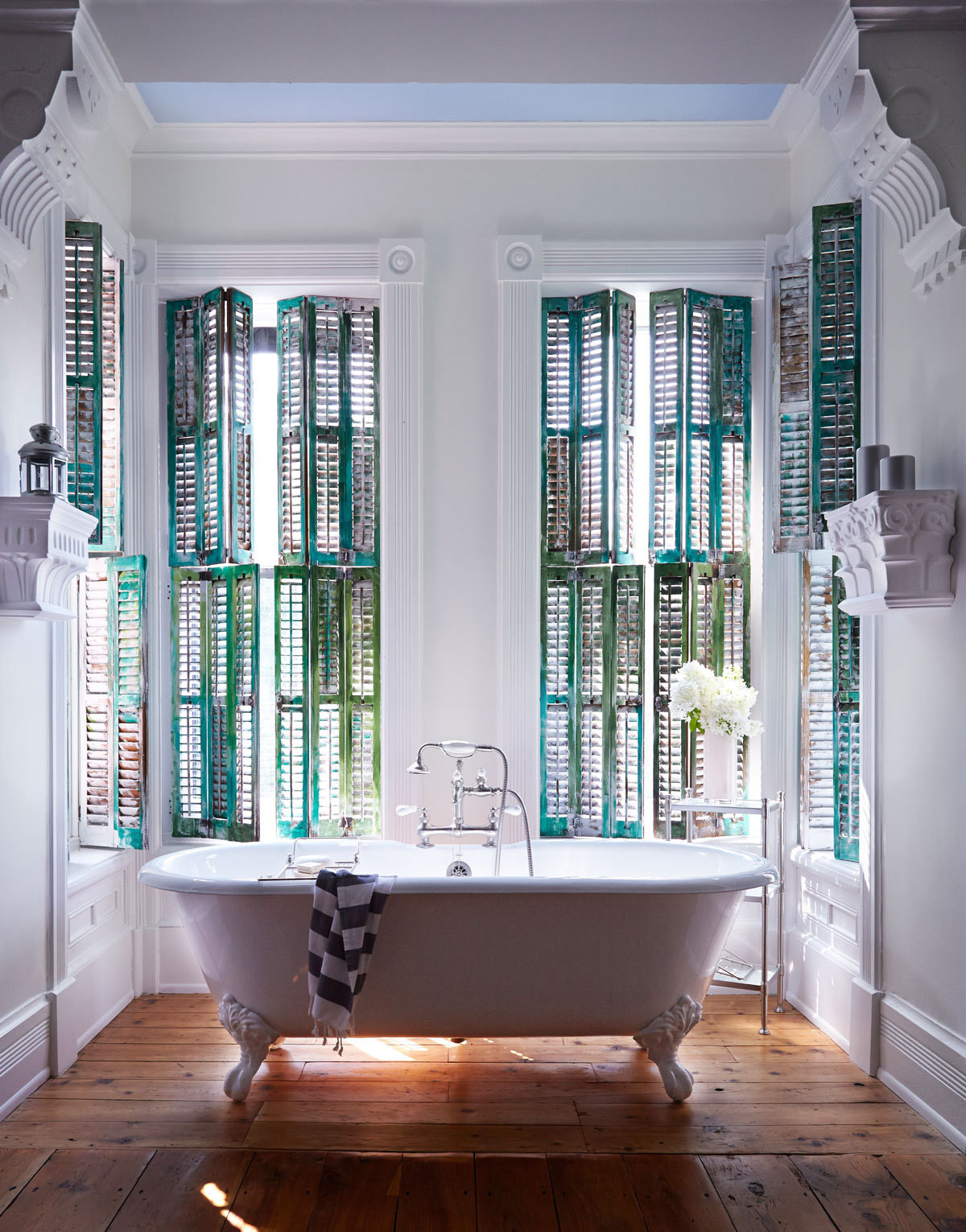 Moylan's dressing room sits off her bedroom, and features a shapely claw-foot tub surrounded by shutters she painted herself in varying shades of green.