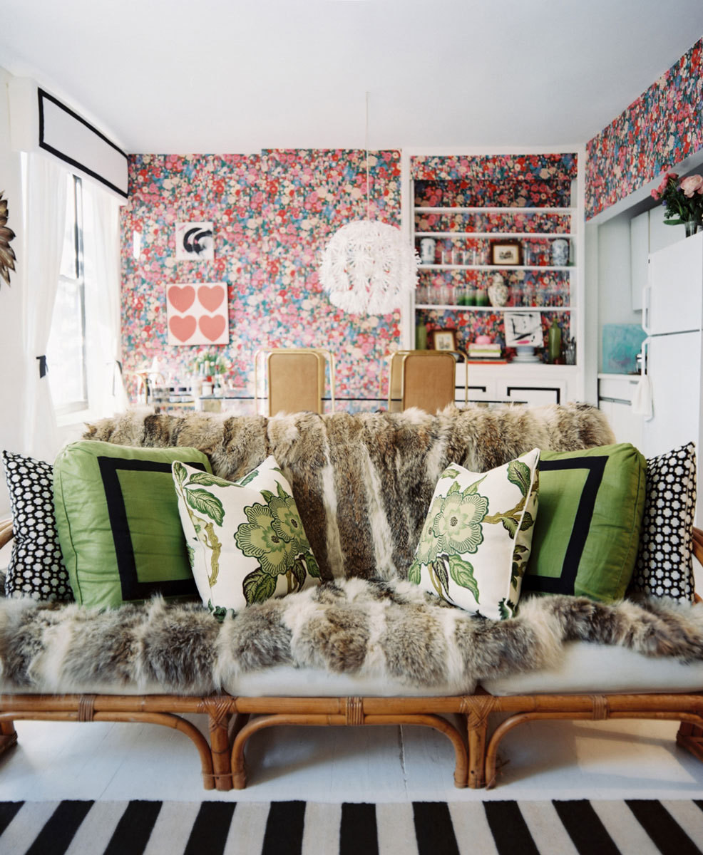 Floral and graphic pillows top a fur-covered bamboo sofa in the living room. Behind the seating area is a glass-topped brass dining table used as a kitchen island and a DIY workstation.