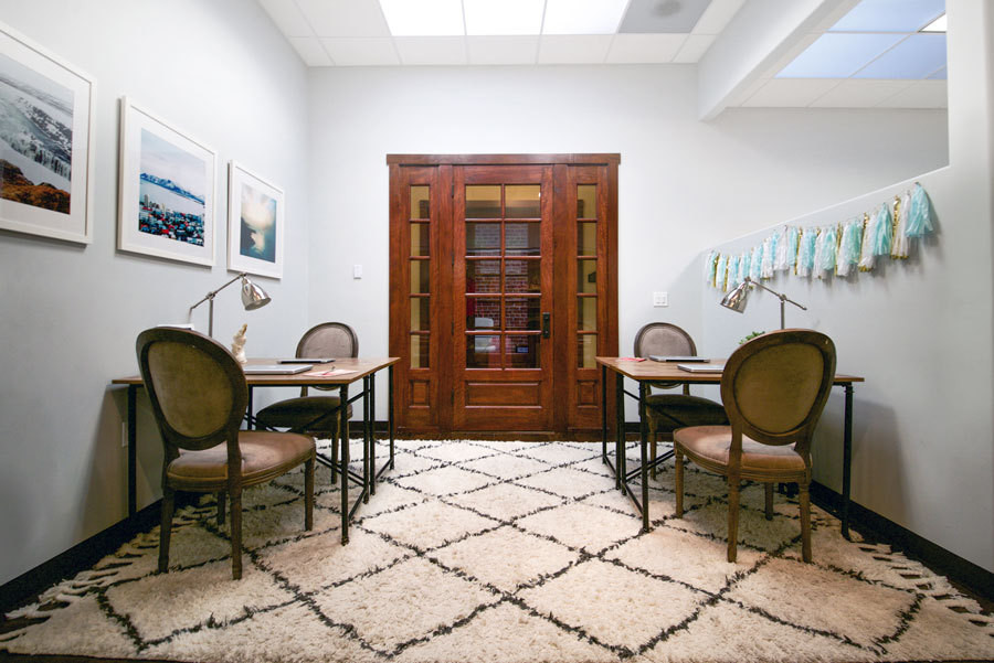 In her team's shared desk area, a Moroccan-inspired area rug (similar style shown here) grounds the space. The white-framed photographs were taken by Hammond on a recent trip to Iceland.