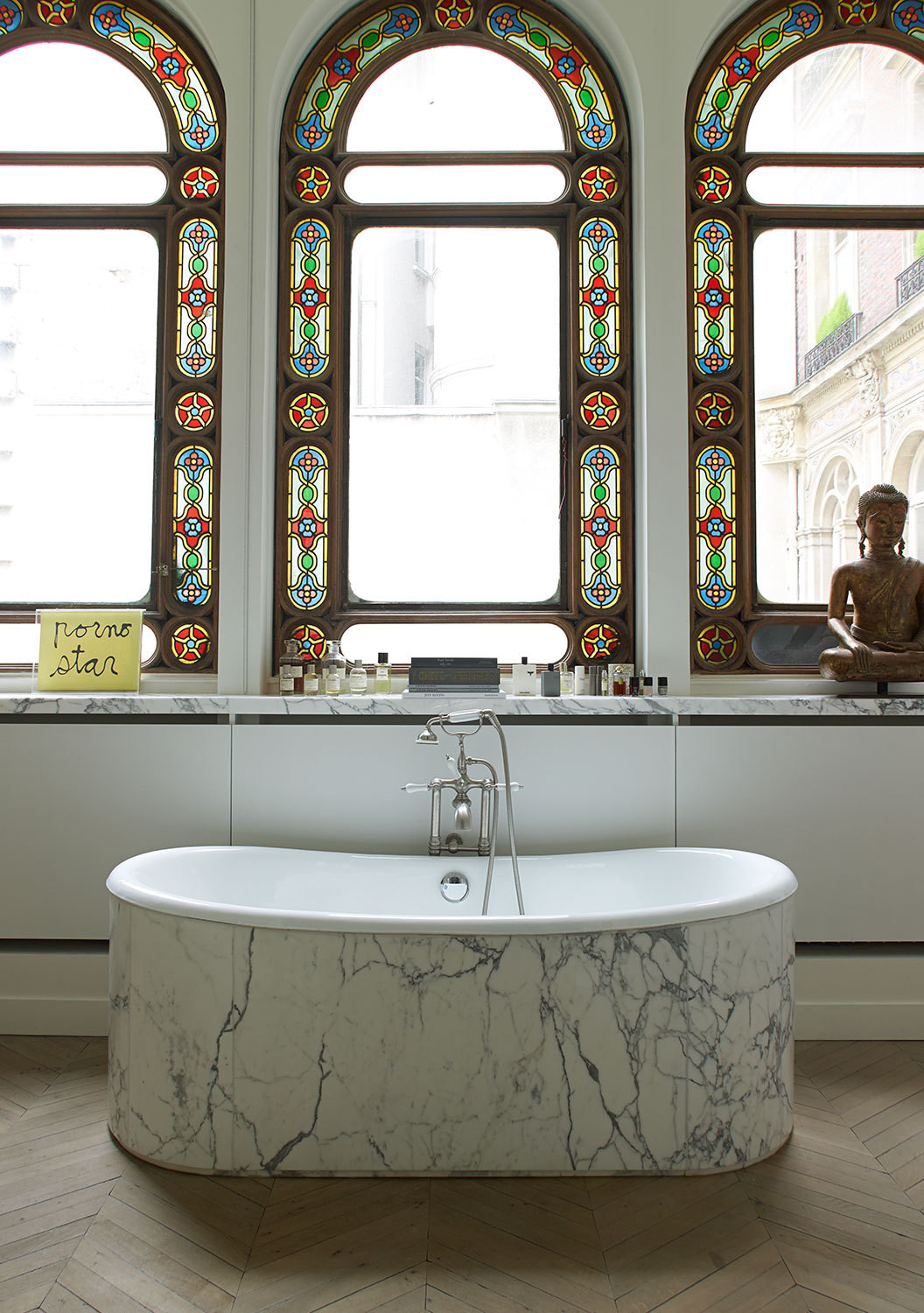 Original stained-glass windows above a soaking tub clad in Calacatta marble.
