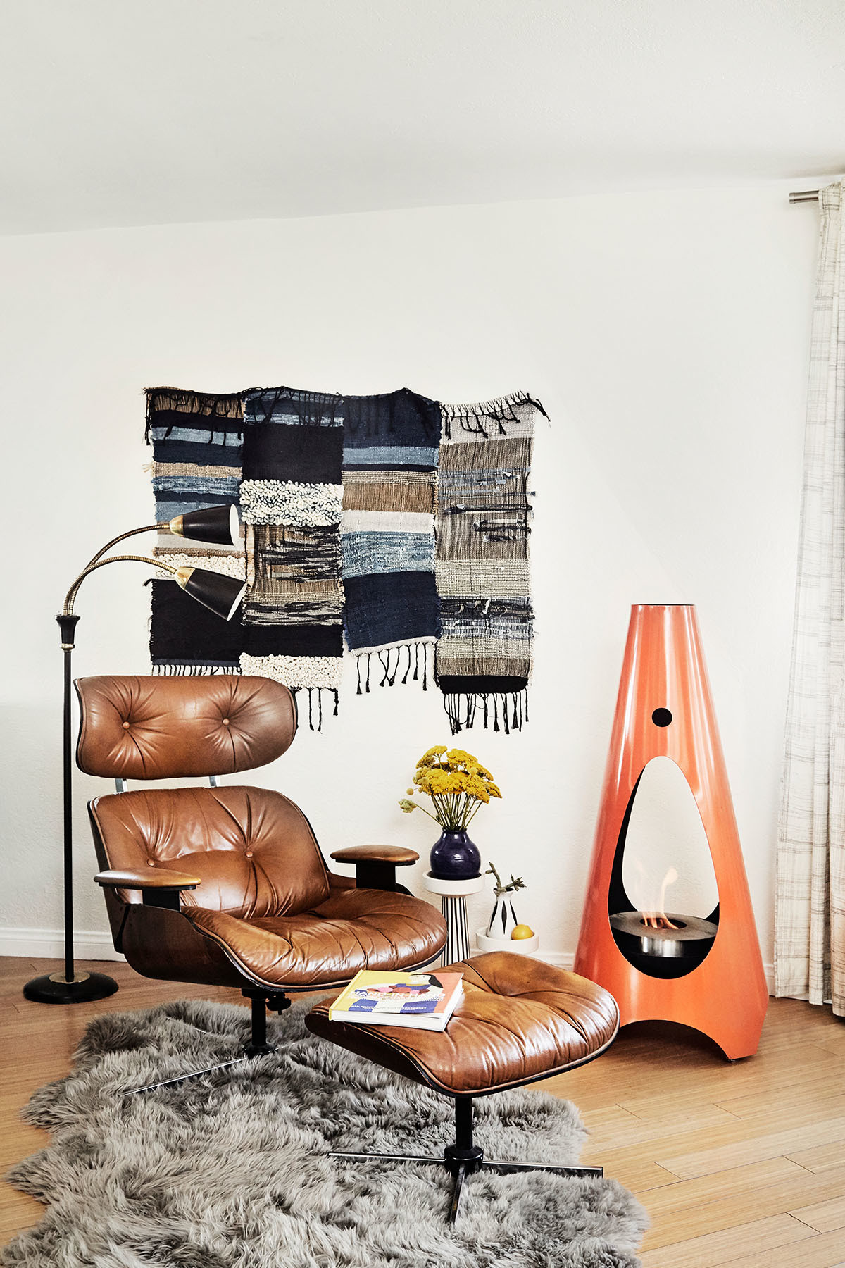 An Eames Lounge Chair and Ottoman (sourced via Pasadena Antique Center) adhere to Calter's Cali-cool, eclectic style. Horne Fireplace | Overland Sheepskin | Janelle Pietrzak Wall Hanging | Vintage Lamp.
