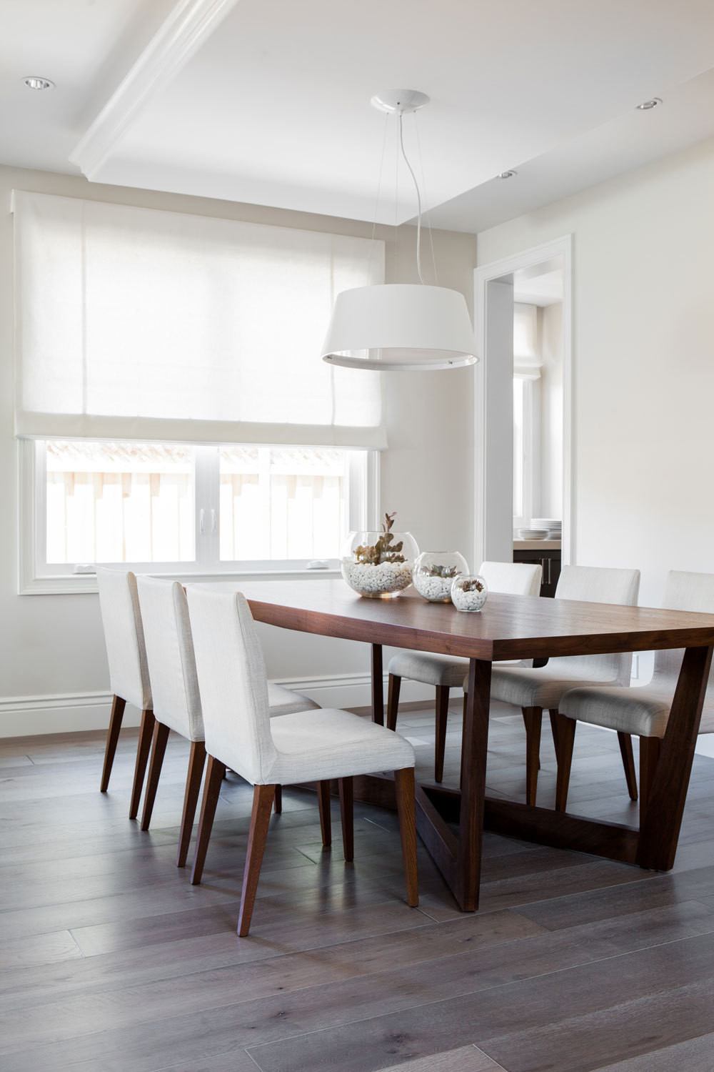 A walnut table from 7th & Seventh Designs anchors the otherwise pale dining room.