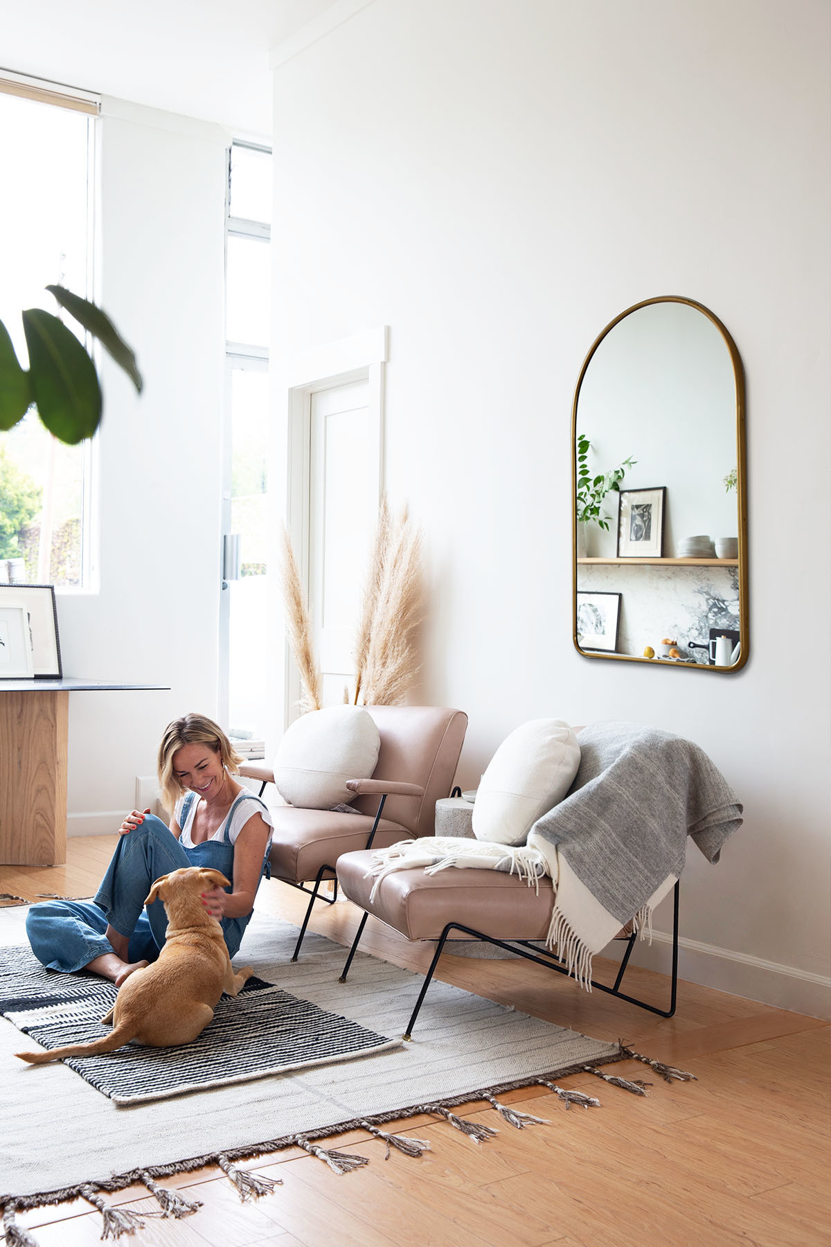 Nelson spent a year on the hunt for her ideal office space, adding a kitchen and busting down walls to ensure the studio floods with natural light. CB2 Rug | Vintage Rug | Chairish Vintage Armchairs| West Elm Pillows | HD Buttercup Throw | Zachary A Design Side Table | Rejuvenation Mirror.