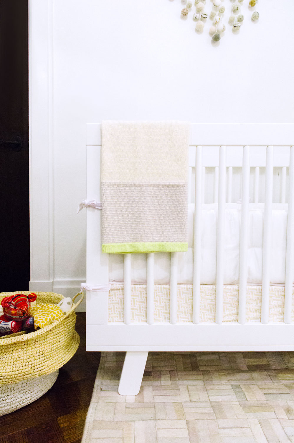 Serene & Lily's Hudson crib is a streamlined compliment toa slouchy woven basket and texturedcarpet.