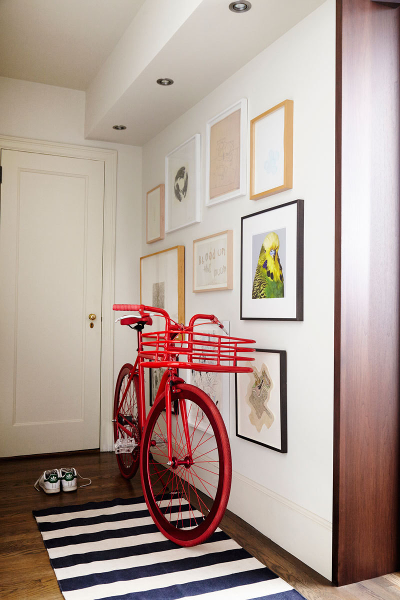 A gallery wall and a cherry-red bicycle on a graphic black-and-white rug create a vibrant display in the apartment's entry area.