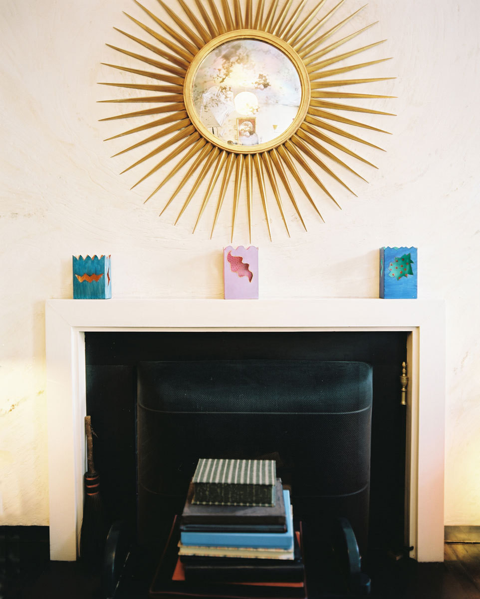 A gold starburst mirror hangs above a narrow mantel.