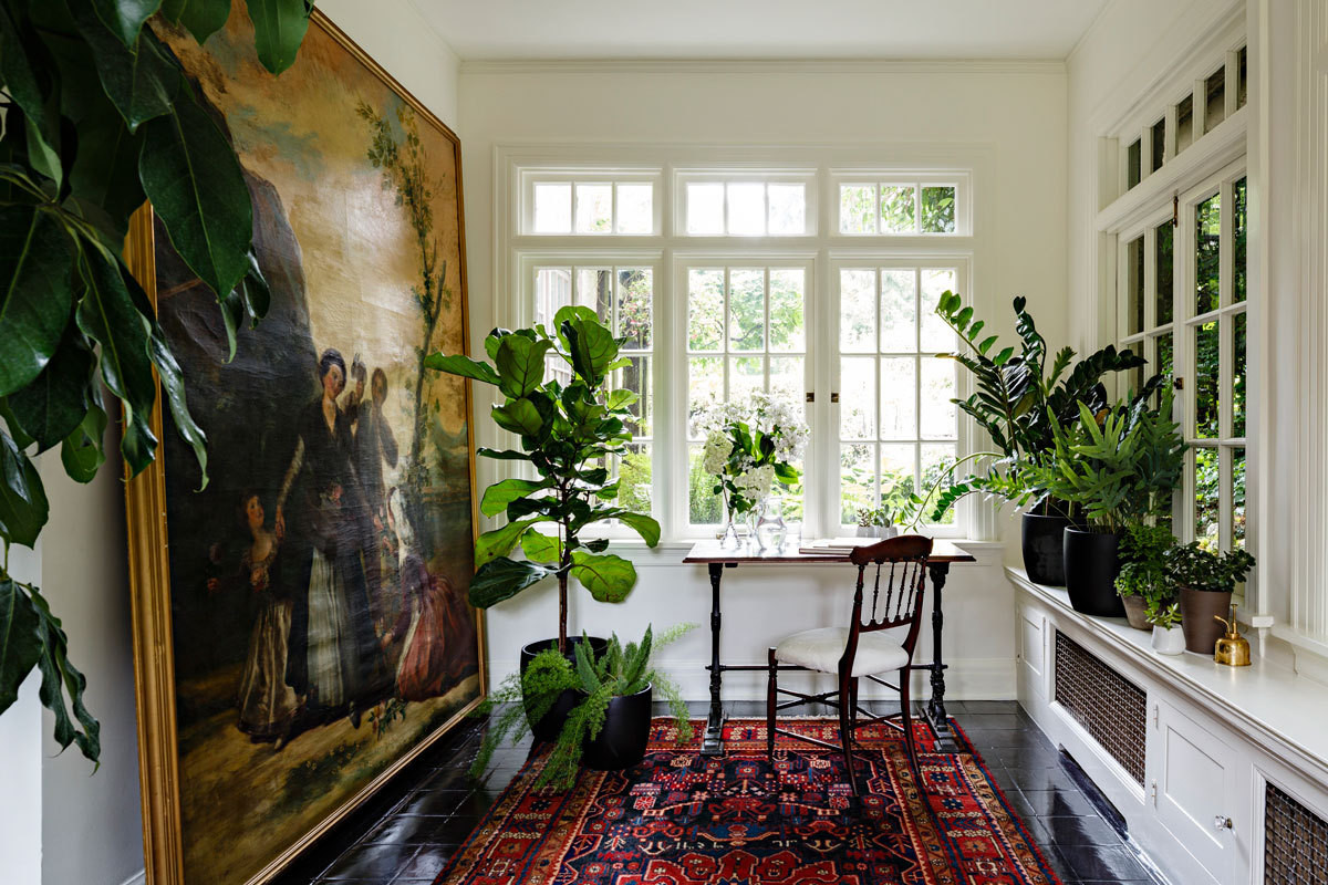 The greenhouselike feel of the sunroom is enhanced by an abundance of plants and set off by subtleantiques and an oversize painting.