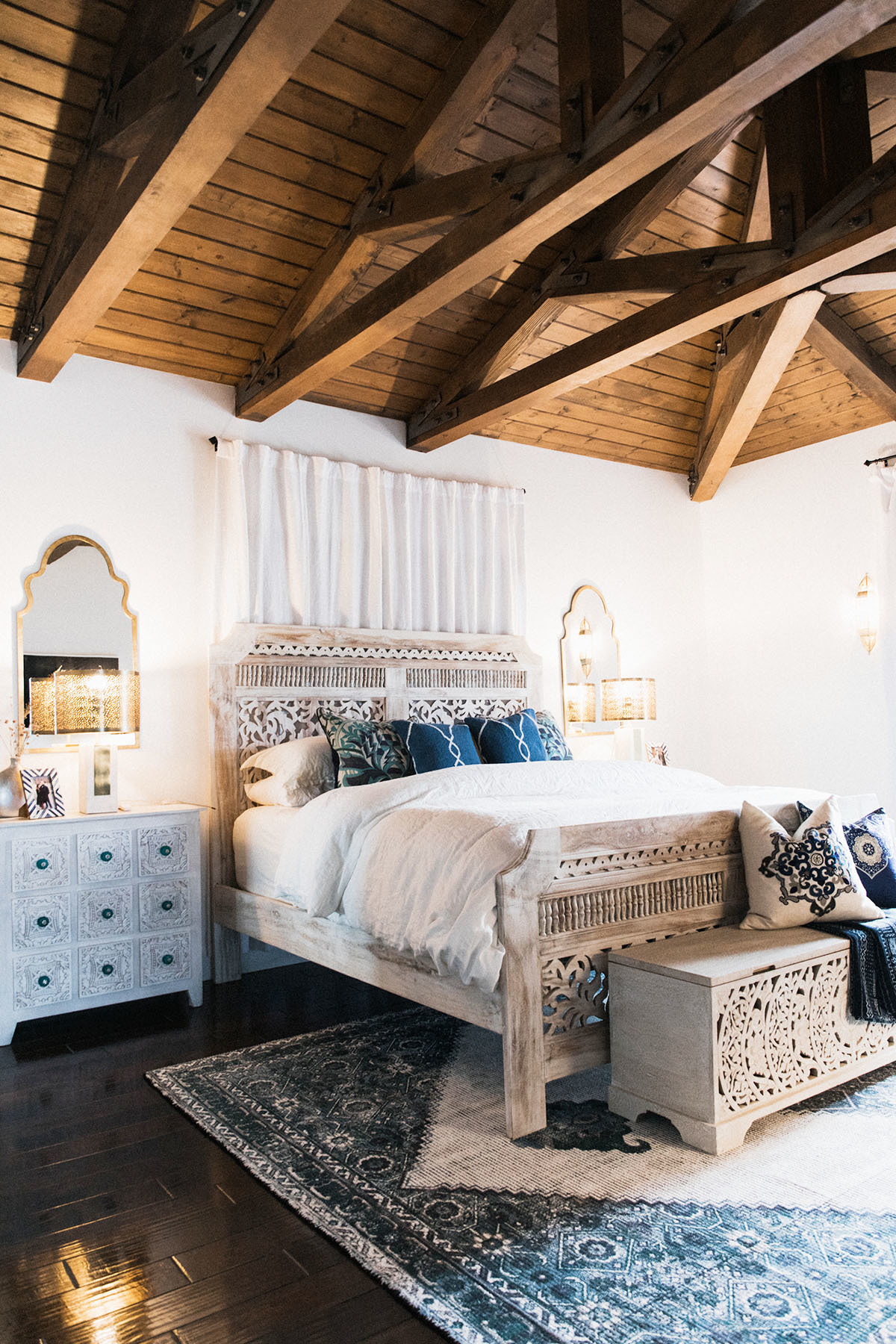 Shahid layers the master bedroom space with a jewel-toned rug and whitewashed wood. Benjamin Moore Paint | Feizy Rug | Living Spaces Bed | Restoration Hardware Bedding | Antique Bedside Tables | Custom Dresser | LampsPlus Mirrors | Custom Throw | Vintage Pillows | Custom Drapes.