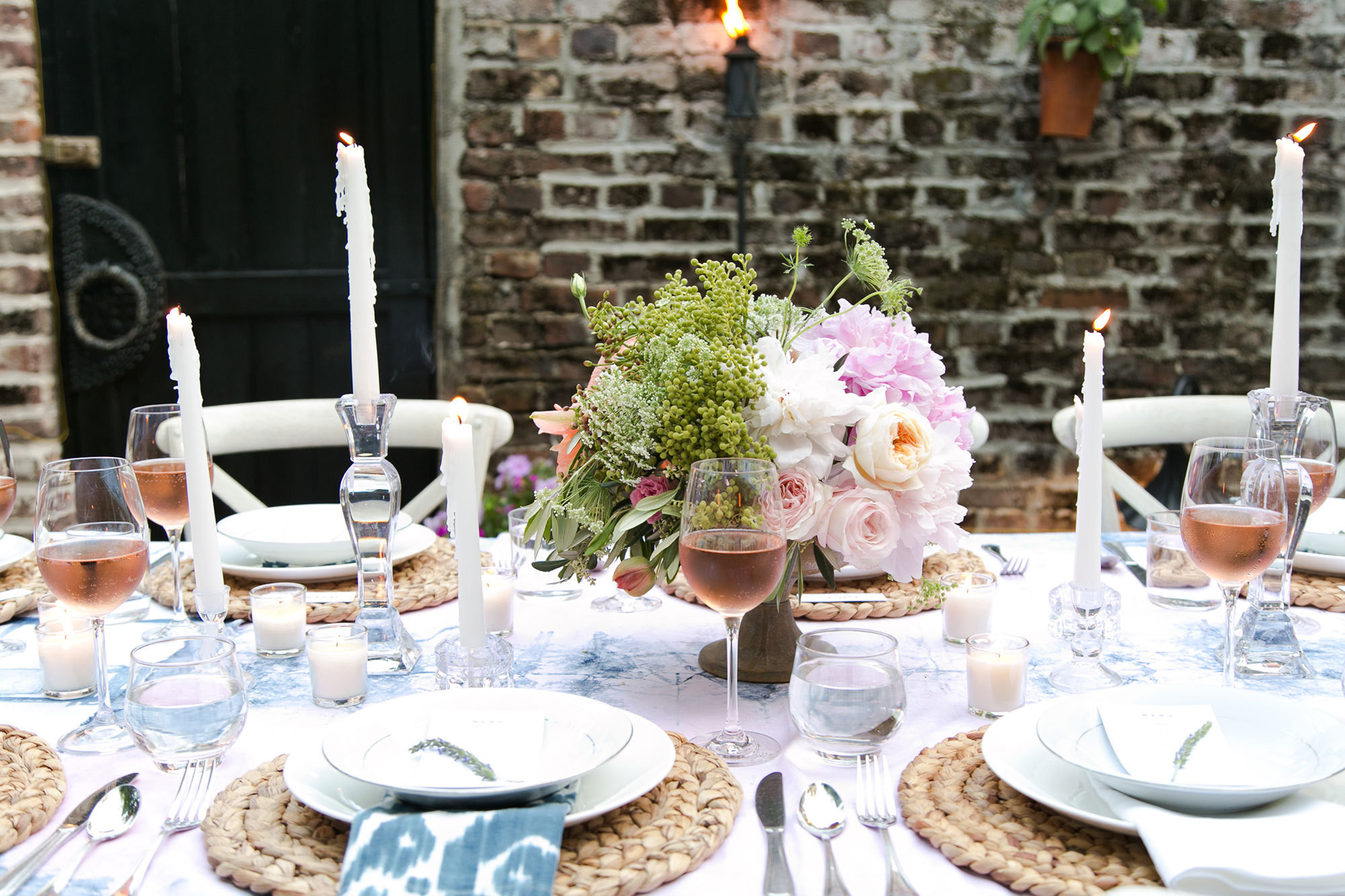 Theromantic tablescape of an outdoordinner party hosted by a group of Charleston creatives. Photography by Lucy Cuneo.