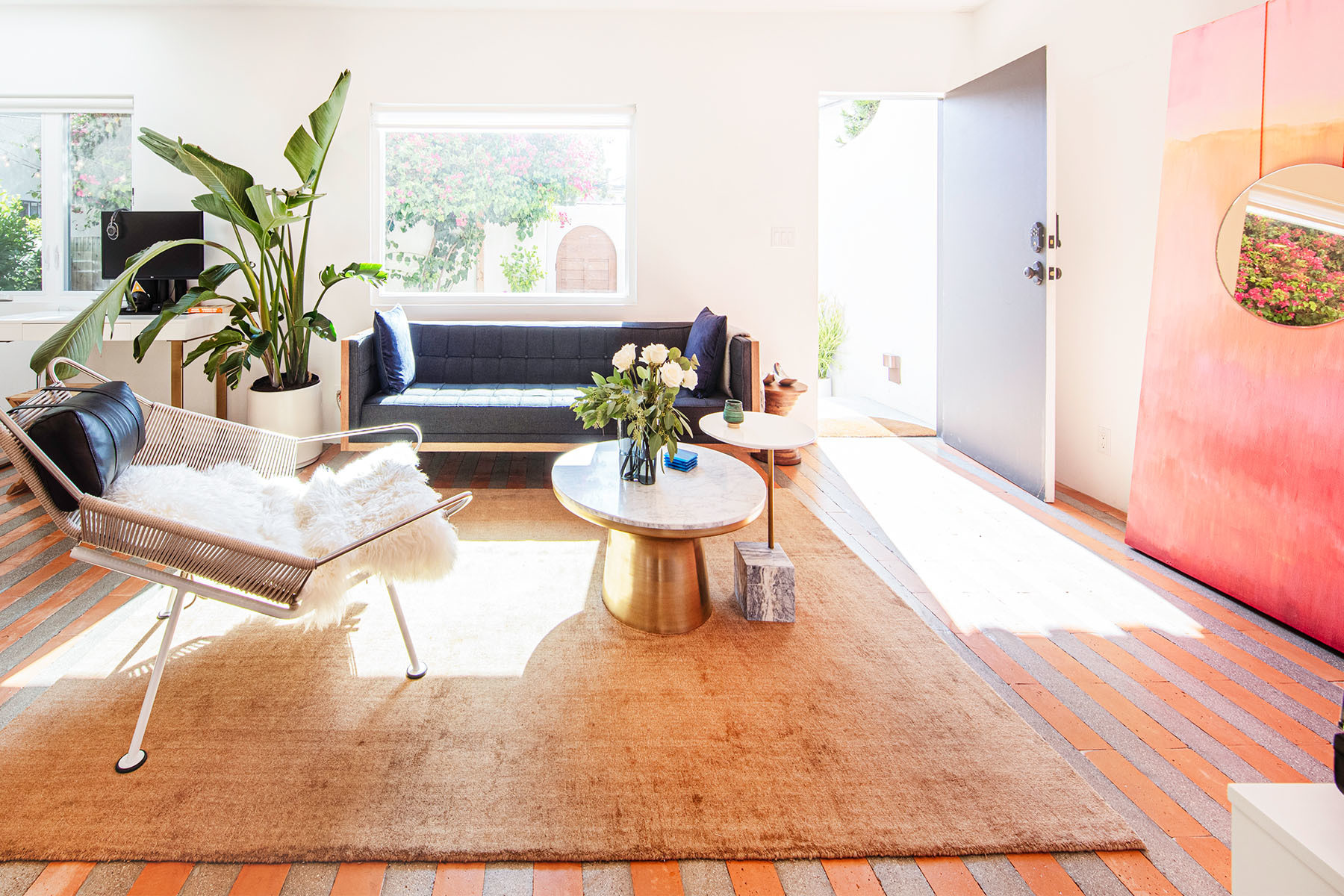 A sunlit living space completes the indoor-outdoor vibe for this L.A. jewelry designer. Flag Halyard Armchair | West Elm Rug | West Elm Mirror | Mounser Studio Artwork | IKEA Shelves | Vintage Baskets | West Elm Coffee Table | Georg Jensen Bowls | Alvar Aalto for Iittala Planters.