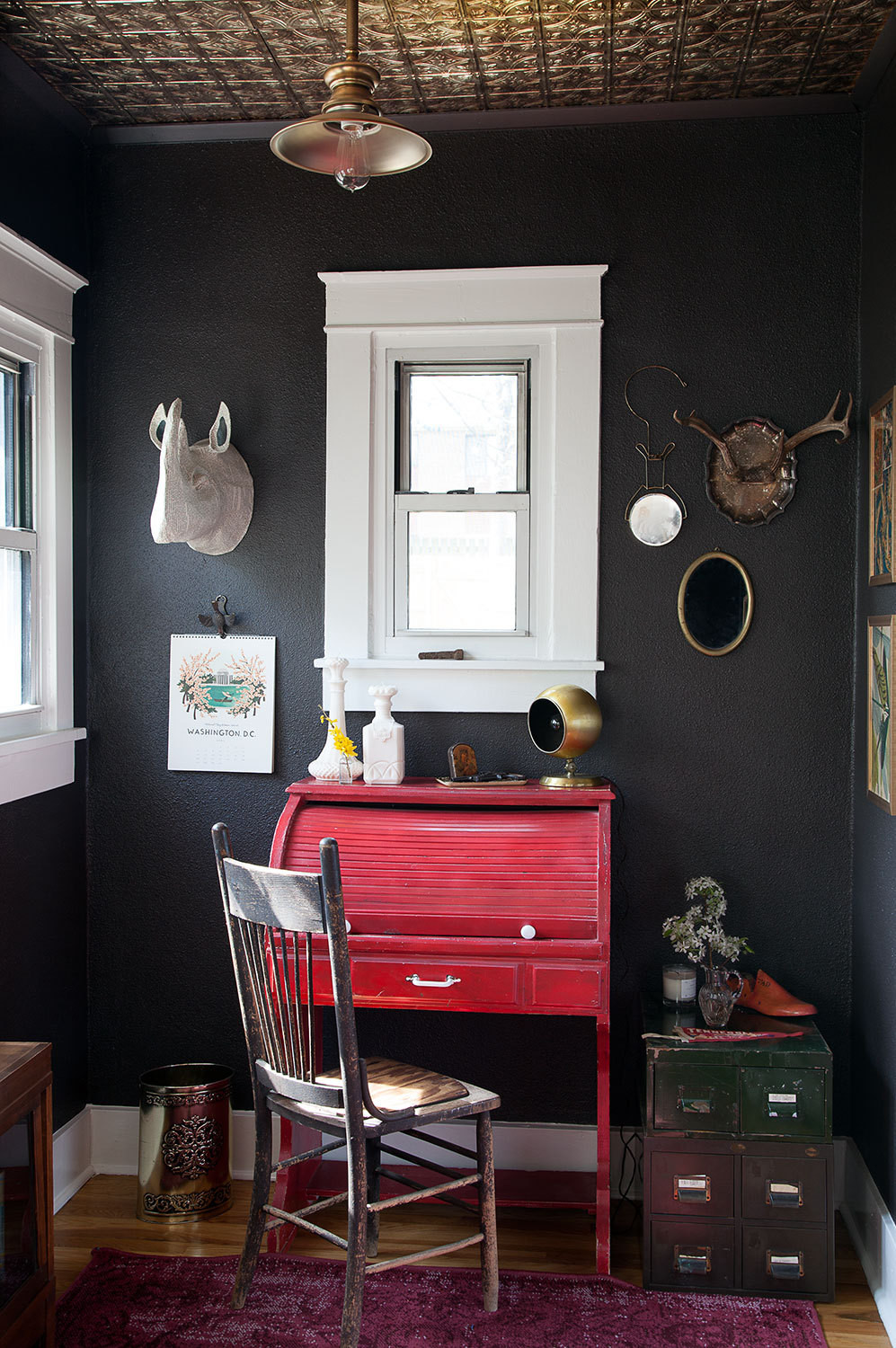 Black walls and a gold faux-pressed-tin ceiling make the tiny office a dramatic focal point.