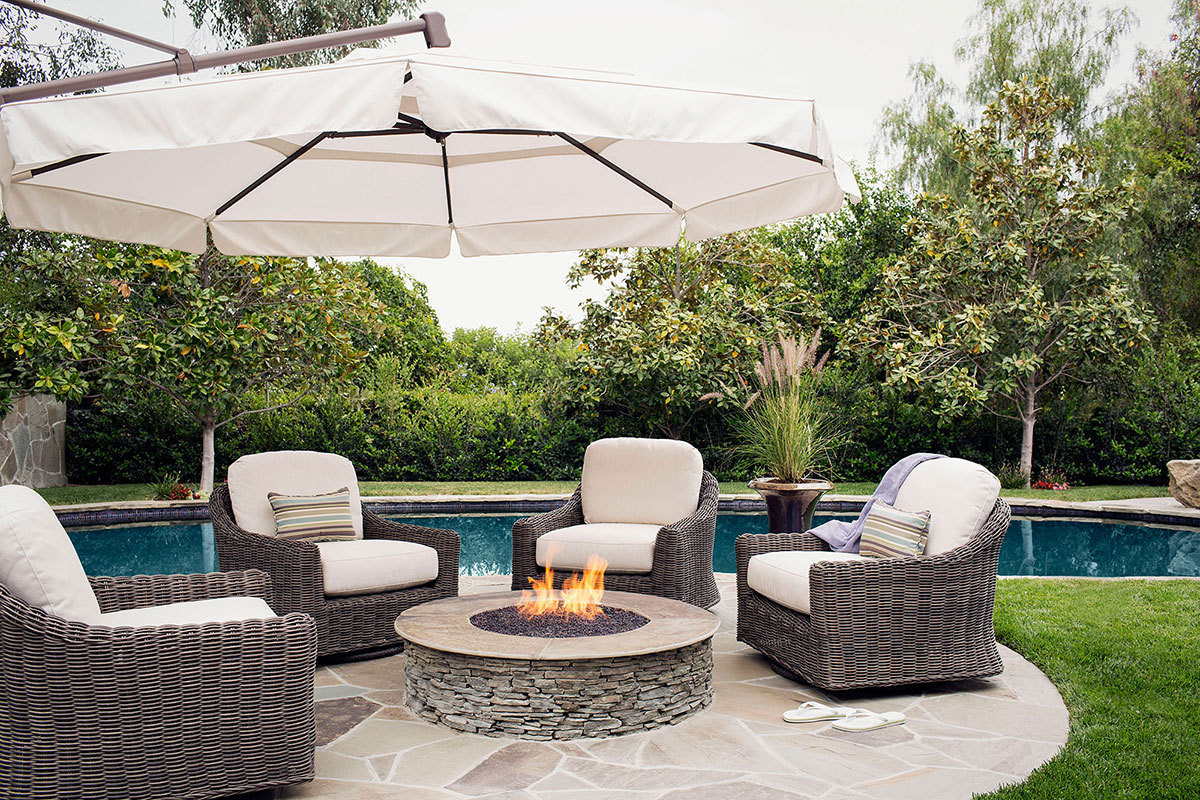 An outdoor seating area composed of four all-weather Huntington Swivel Chairs around a firepit grounds a circular stone patio by the pool.