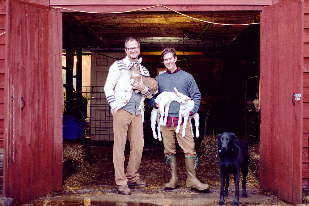 Josh Kilmer-Purcell and Brent Ridge outside their barn with their baby goats and a pyrenees-labrador mix they rescued near Kingston, N.Y.