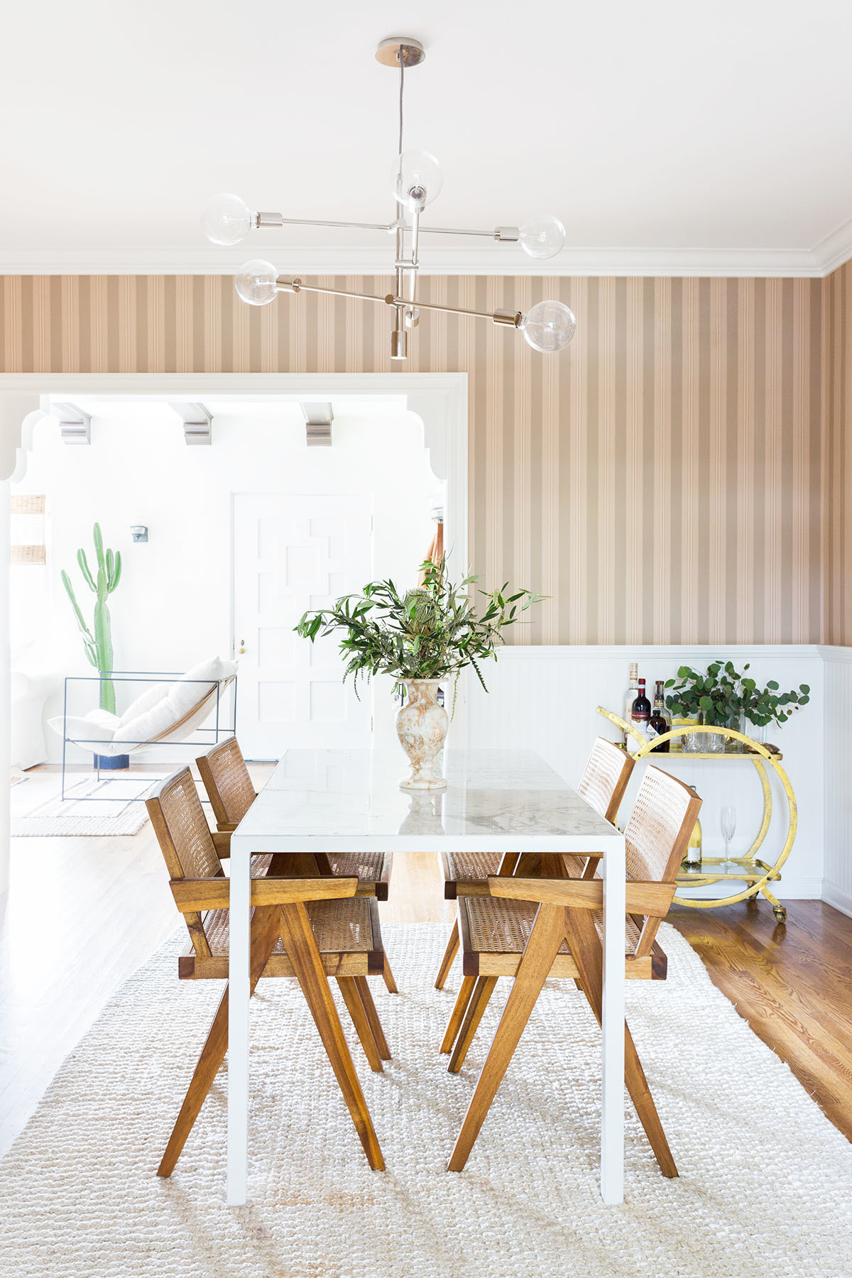 The couple's dining room boasts pinstriped wallpaper — an original feature they chose not to change after moving in. Vintage Dining Table | Custom Dining Chairs | Vintage Rug | Robert Siegel Studio Vase | Lulu and Georgia Bar Cart.