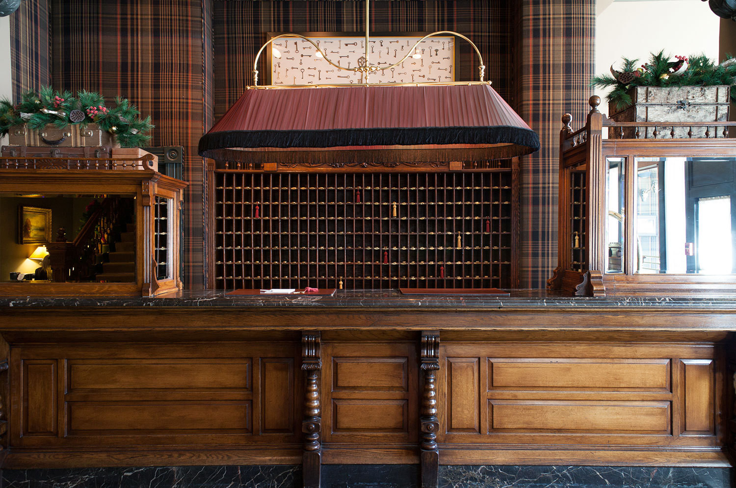 The original front desk dominates a plaid-and-marble-accented reception area.
